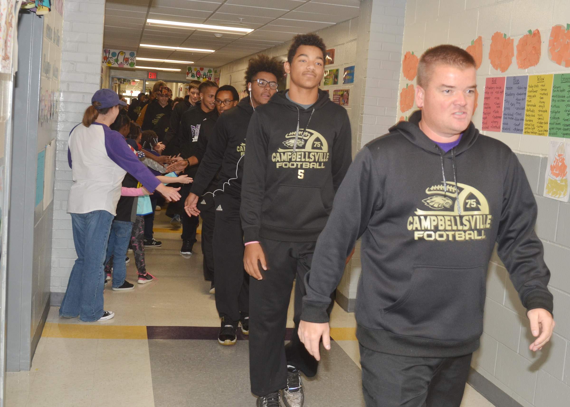 CHS head football coach Dale Estes leads his players down the CES hallway.