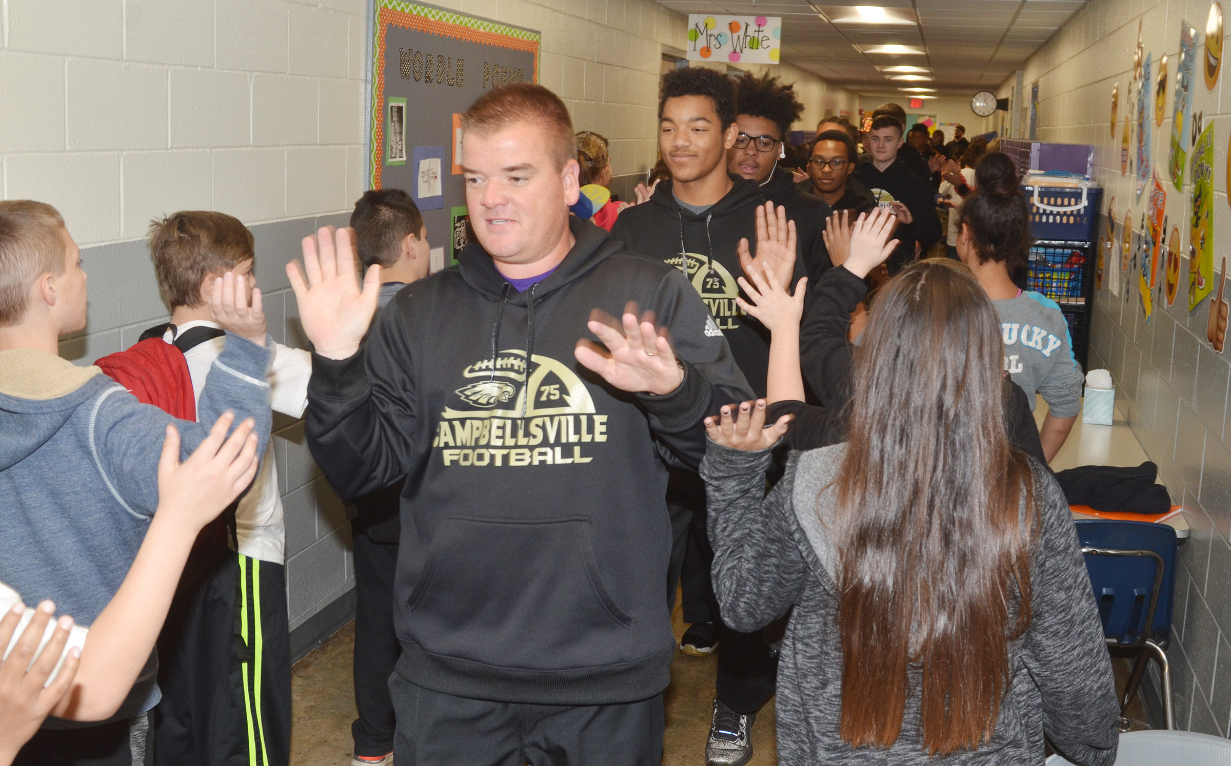 CHS head football coach Dale Estes high-fives CES fifth-graders.
