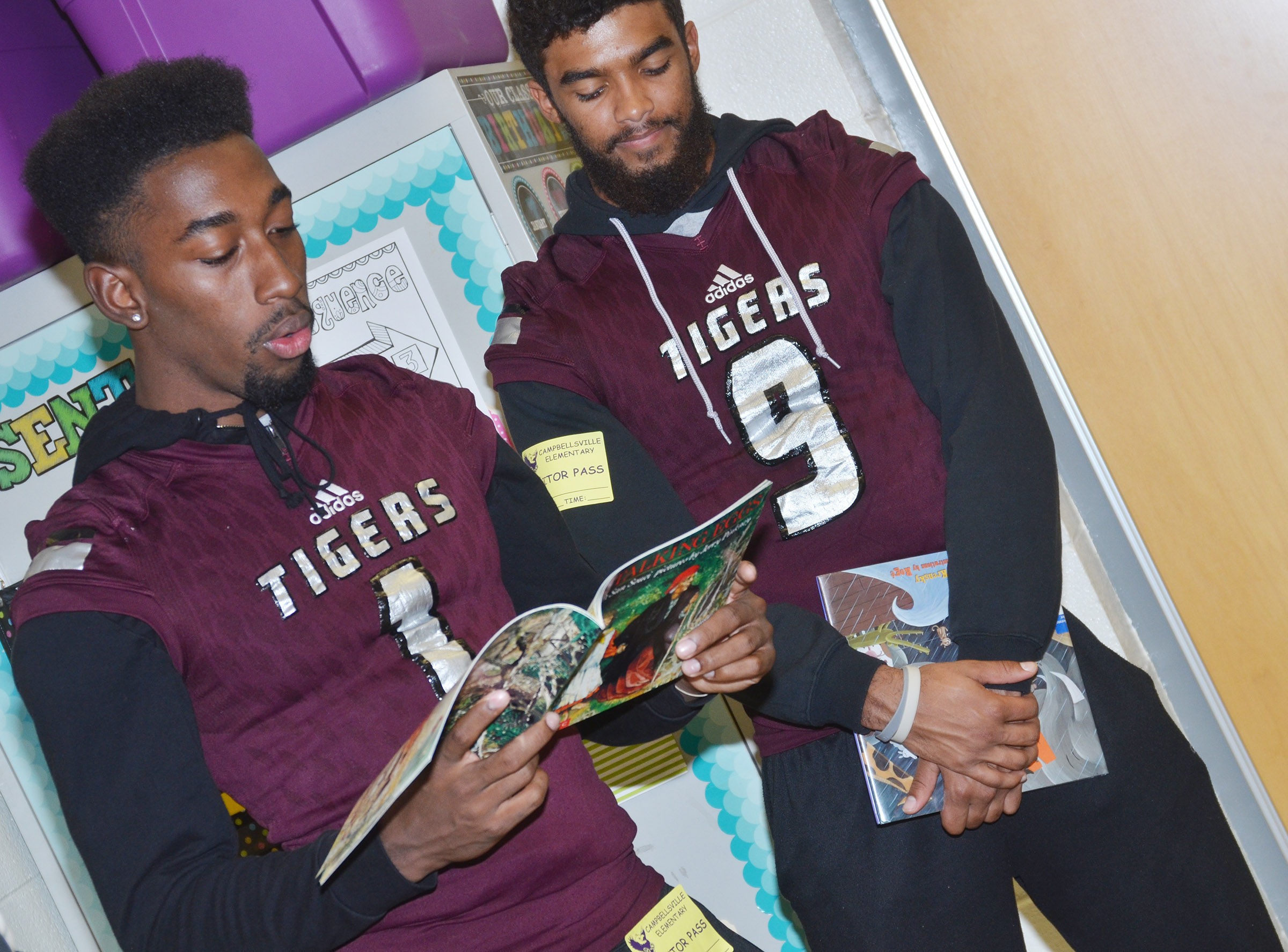 CU player Kendon Young reads to CES fifth-graders. Young graduated from Campbellsville High School in 2016. At right is CU player Brayden Russell.