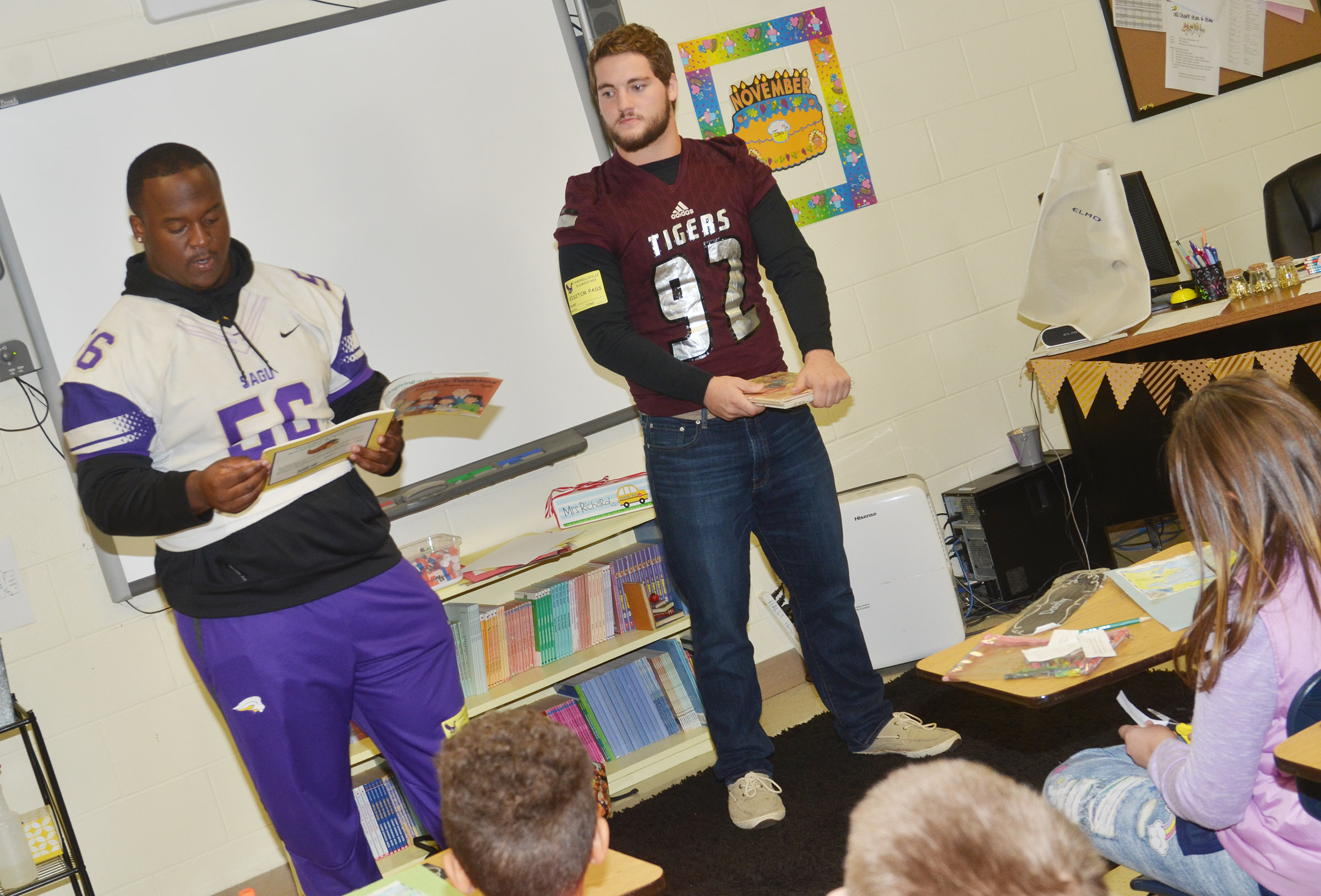 SAGU player Devo McNeal, at left, and CU player Shane Carney read to CES students.