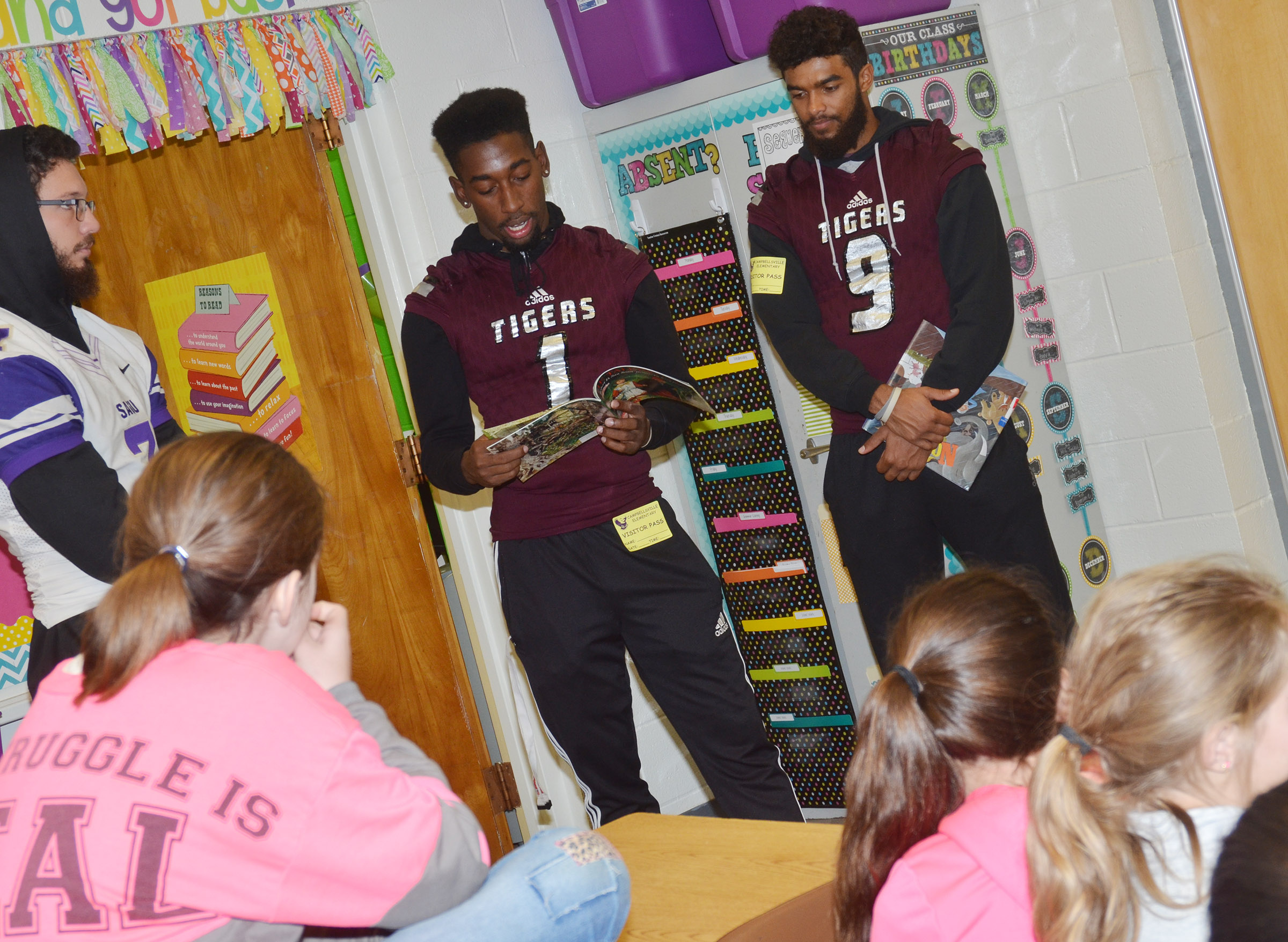 CU player Kendon Young reads to CES fifth-graders. Young graduated from Campbellsville High School in 2016. At left is SAGU player Matt Lighter and at right is CU player Brayden Russell.