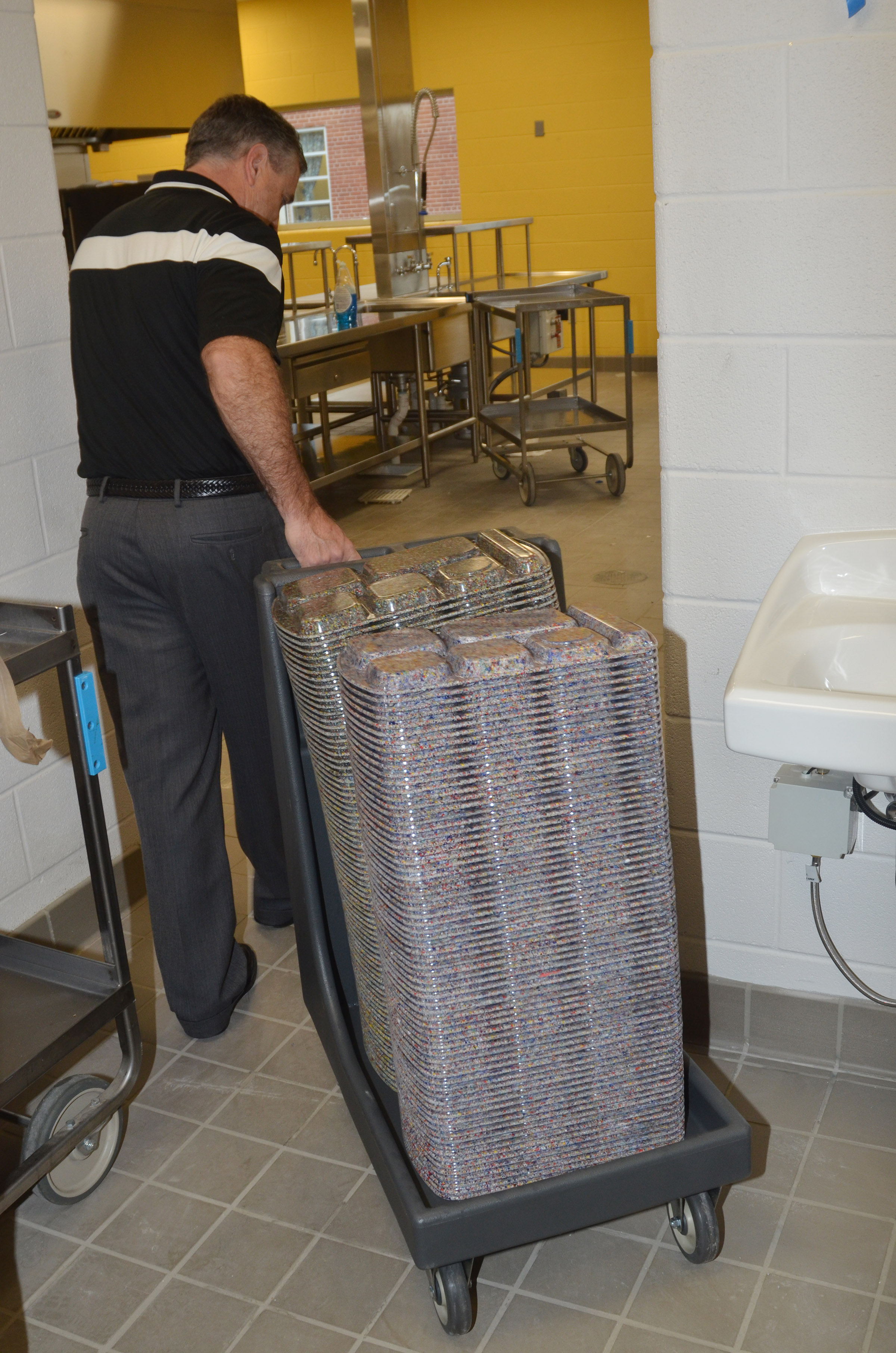 Food Service Director Jeff Richardson loads new lunch trays to be used in the new cafeteria soon.