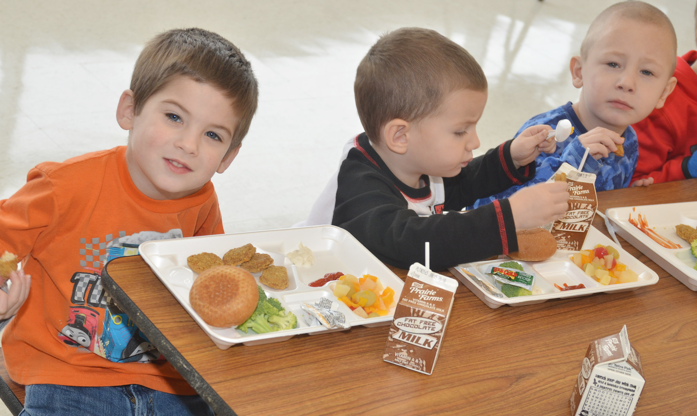 CES preschool students, from left, Charlie Woodbury, Chase Arnett and Cameron Dean were among the first group of students to use the school's new cafeteria.