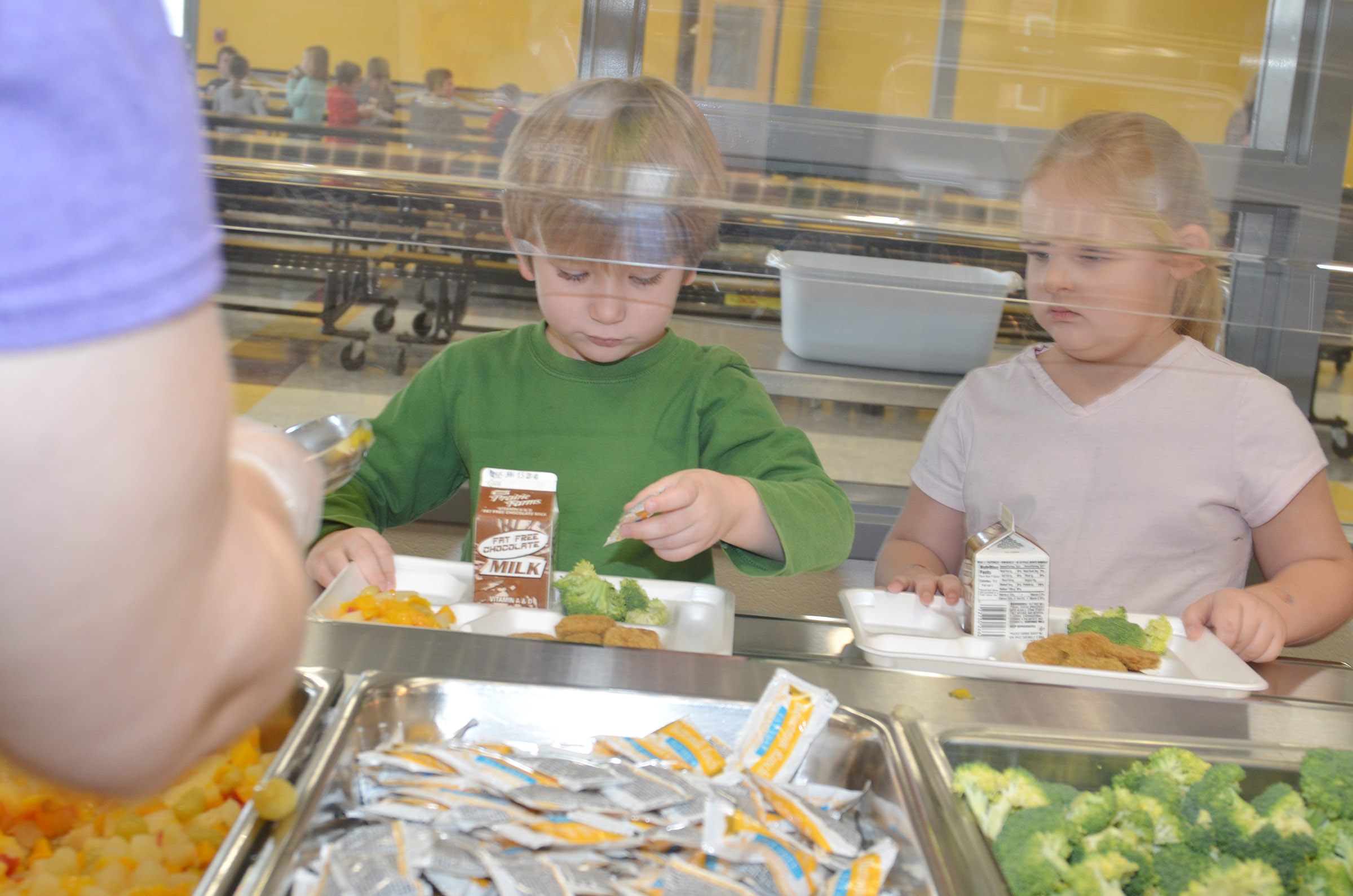 CES kindergartener Luke Banta picks up some ranch dressing in the serving line as he uses the school's new cafeteria for the first time.