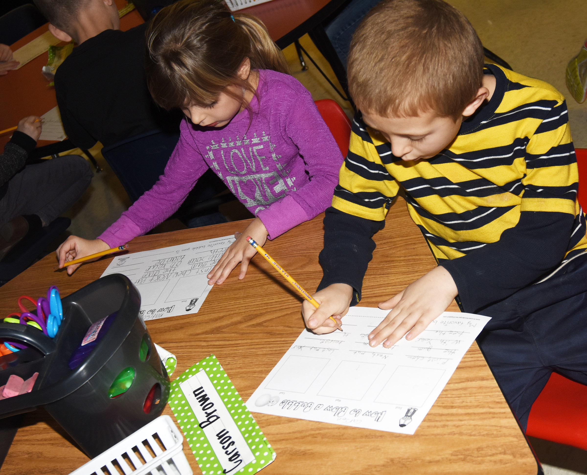 CES first-graders Madison Wilhoite, at left, and Carson Brown write about how to blow a bubble.