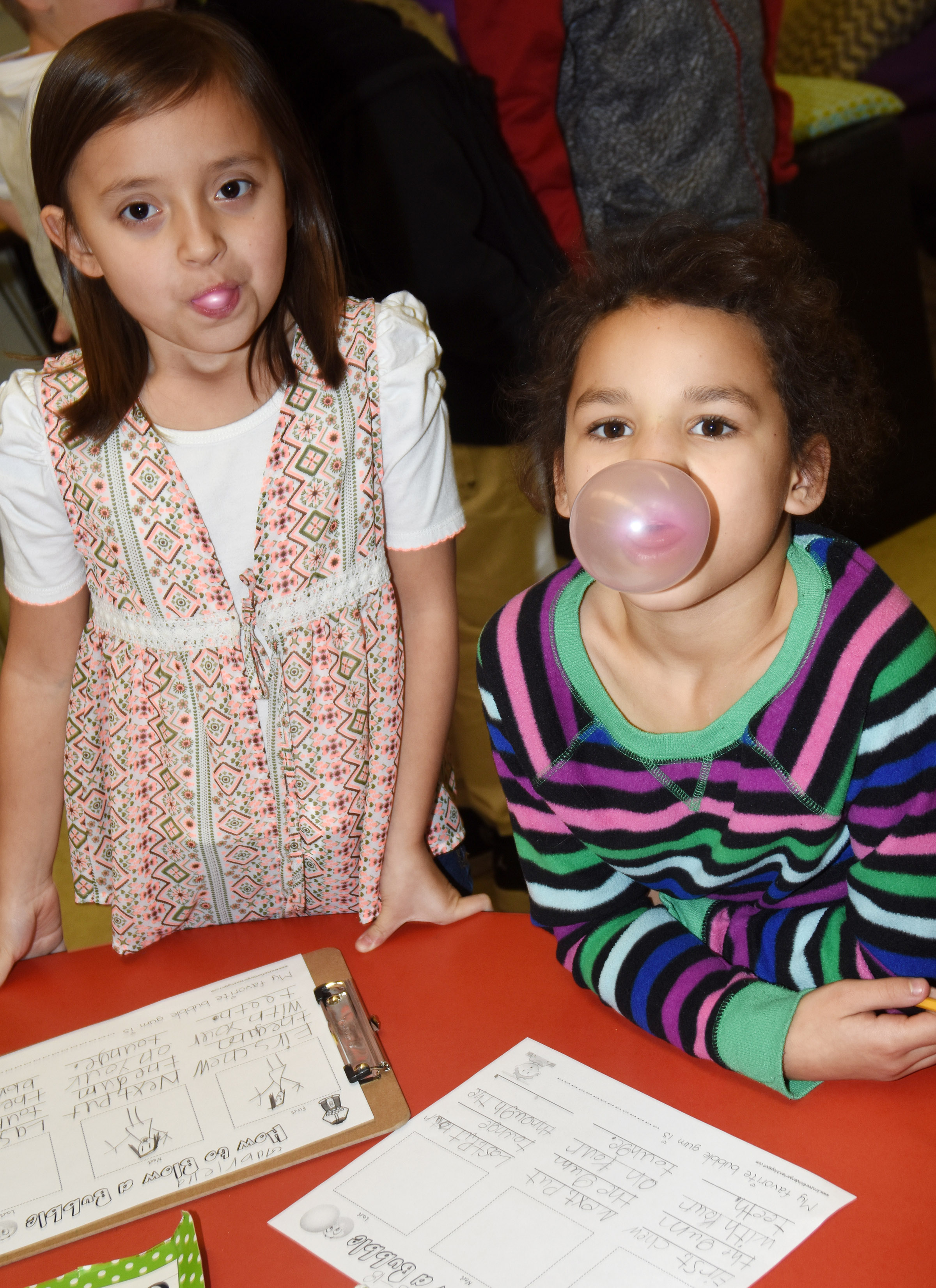 CES first-graders Gabriella Tate, at left, and Aleeya Spaulding blow bubbles.