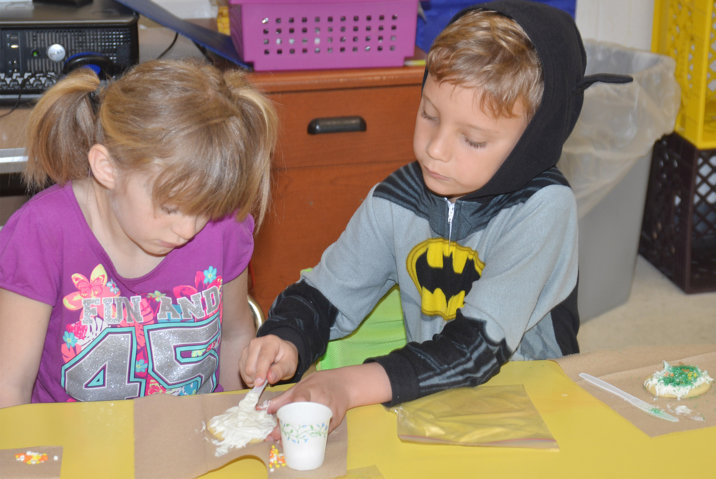 CES first-grader Gabe Prior helps classmates Summer Daniels add icing to her cookie.
