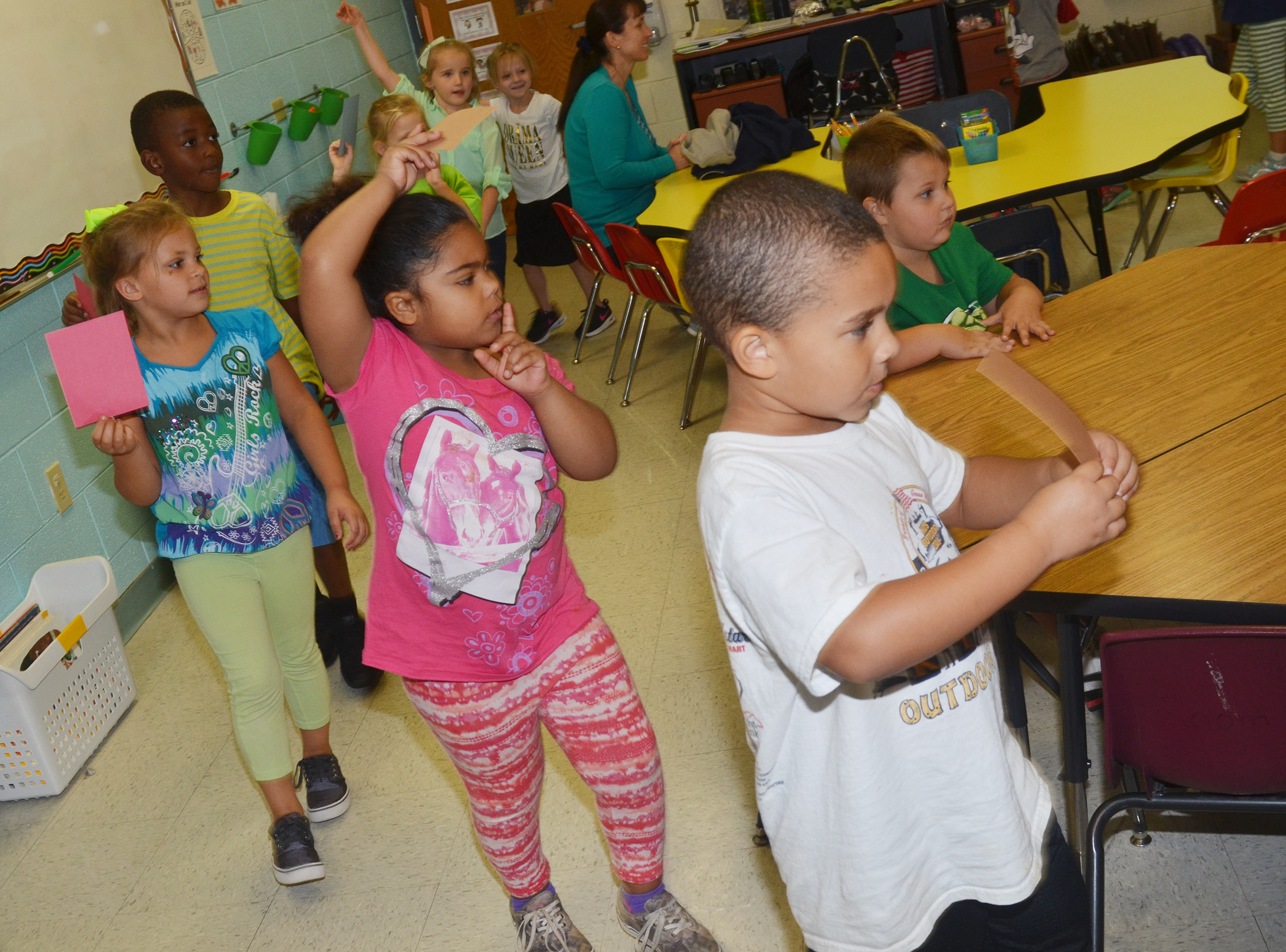 CES kindergarteners walk around their classroom as they hold their papers.