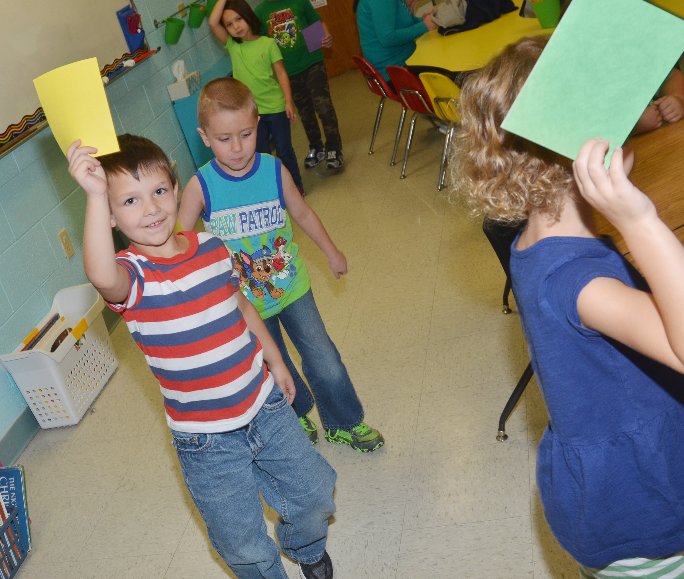 CES kindergarteners, led by Mae Miller, walk around their classroom as they hold their papers.
