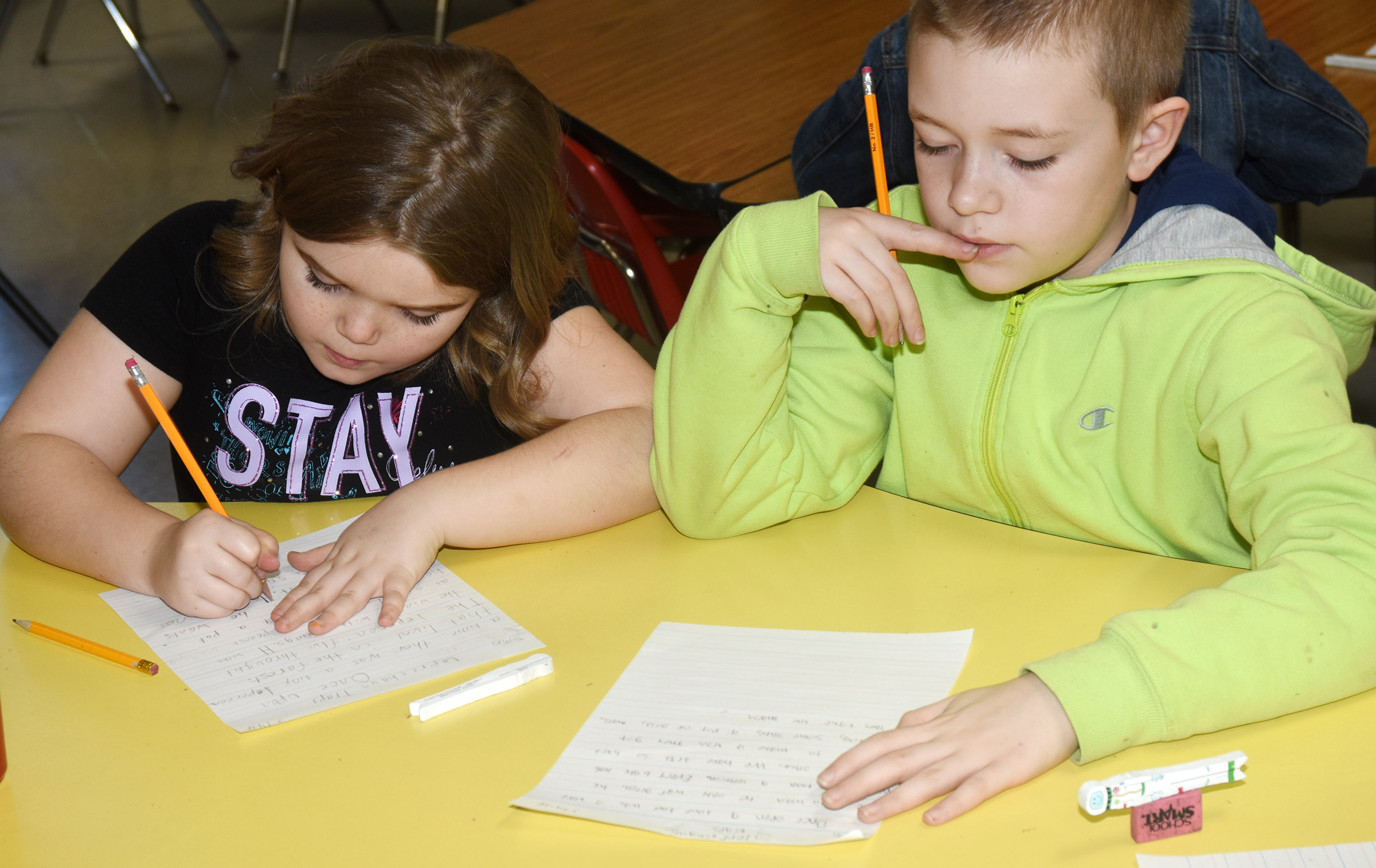 CES third-graders Jaylin Christie, at left, and Alijah Henderson write about how they would catch a leprechaun.
