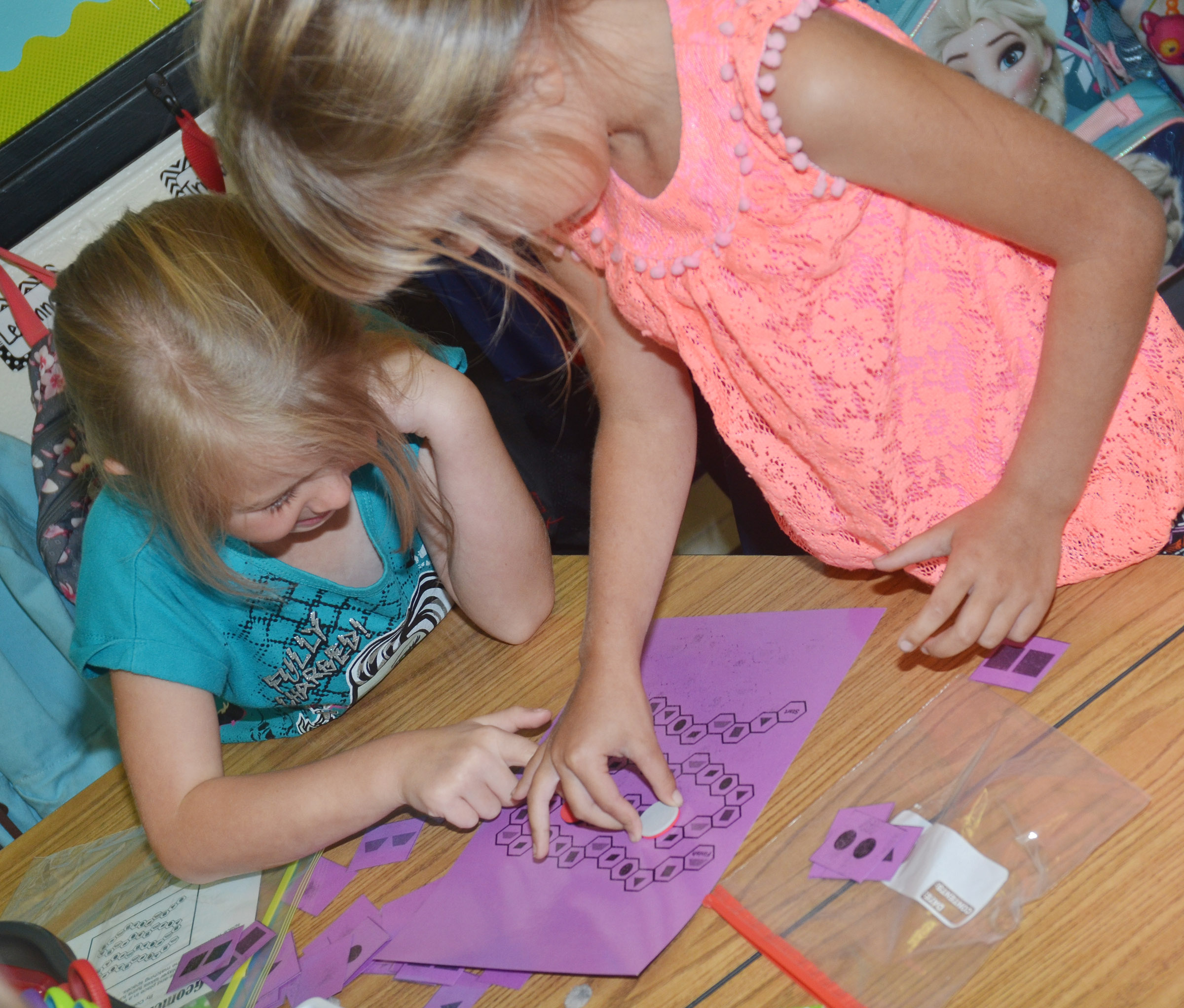 CES first-graders Jewell Brewster, at left, and Madison Wilhoite play a math game together.