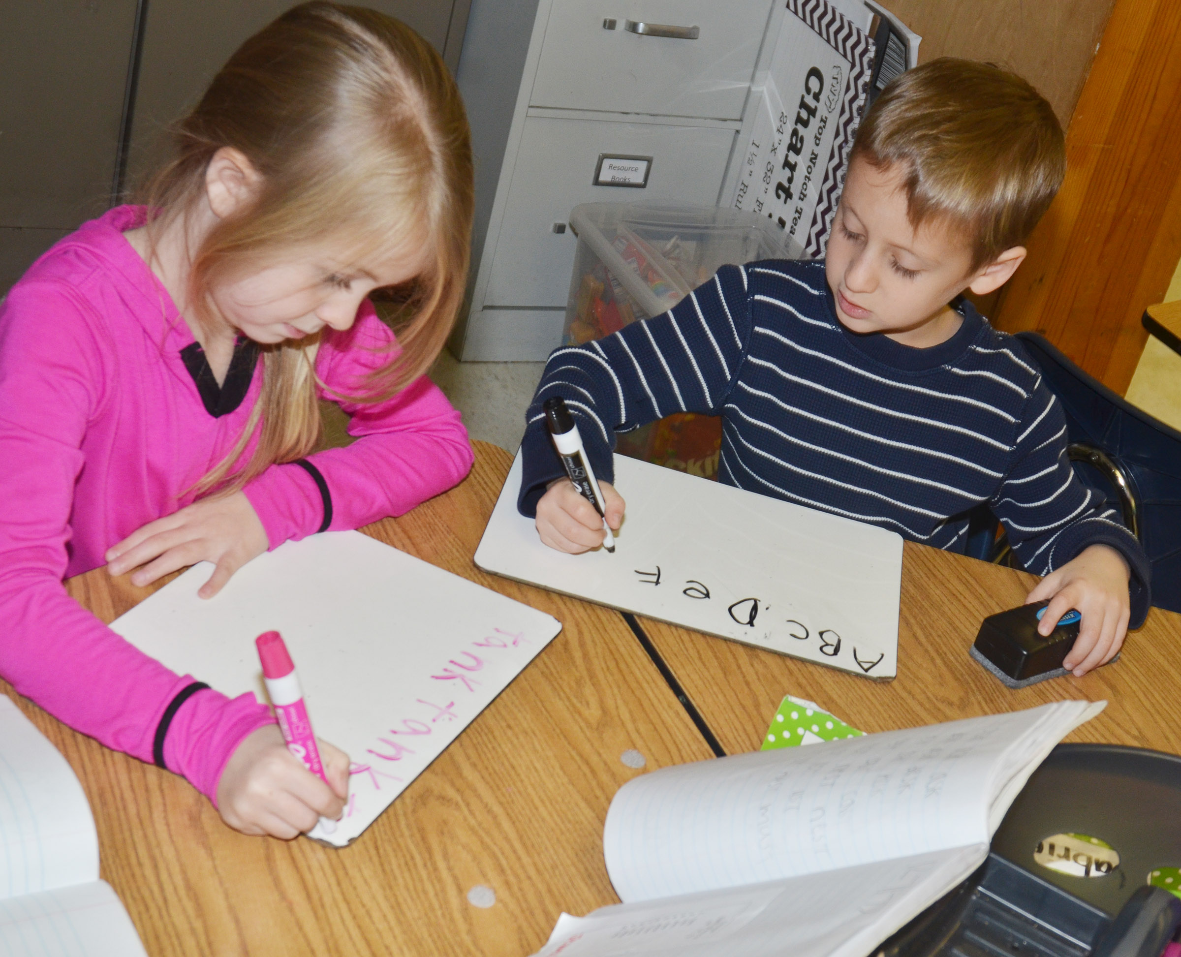 CES first-graders Jewell Brewster, at left, and Gavin Paris practice writing their sight words and alphabet.