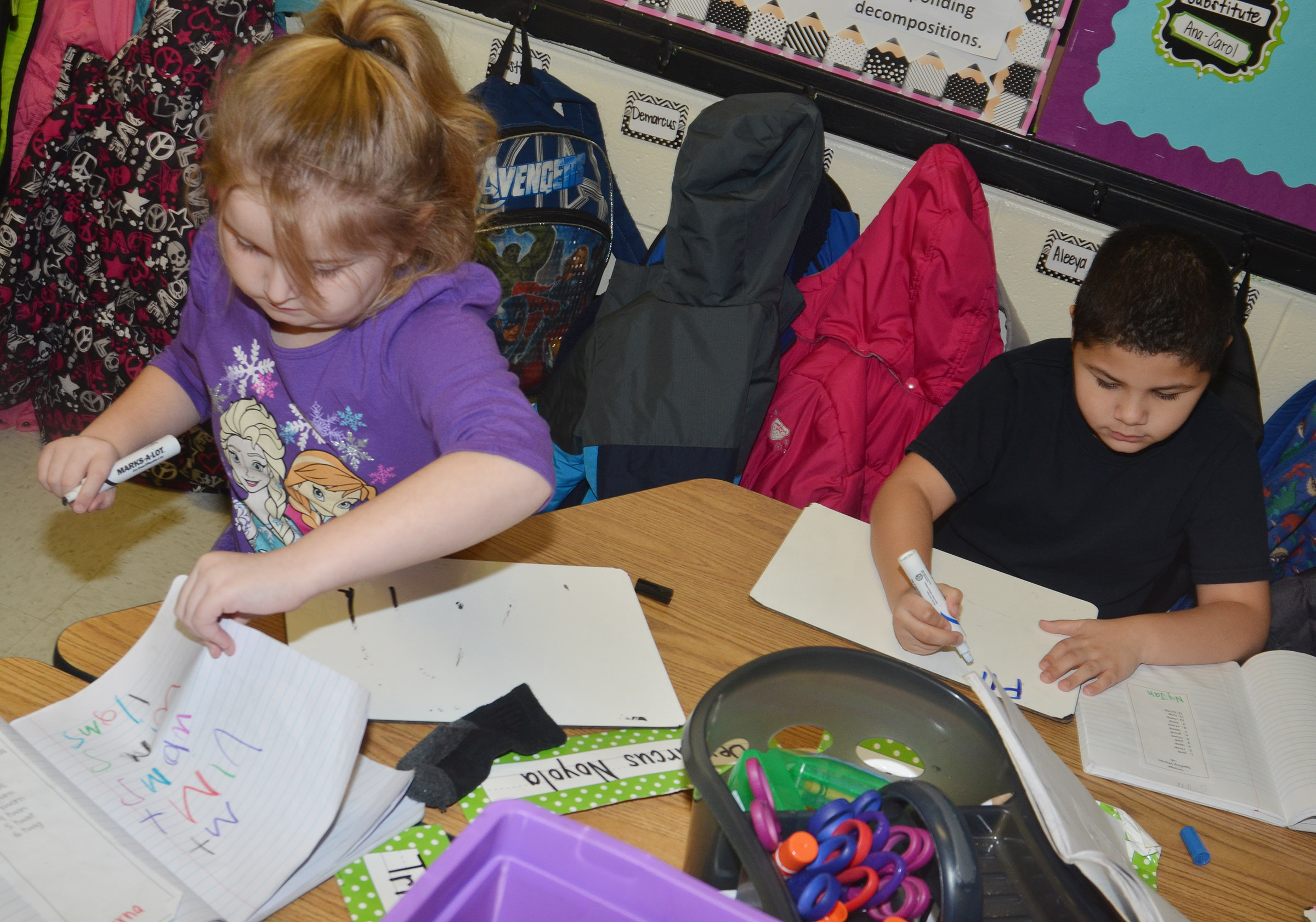 CES first-graders Laurna McKenzie, at left, and NyJah Vaught practice writing their sight words and alphabet.