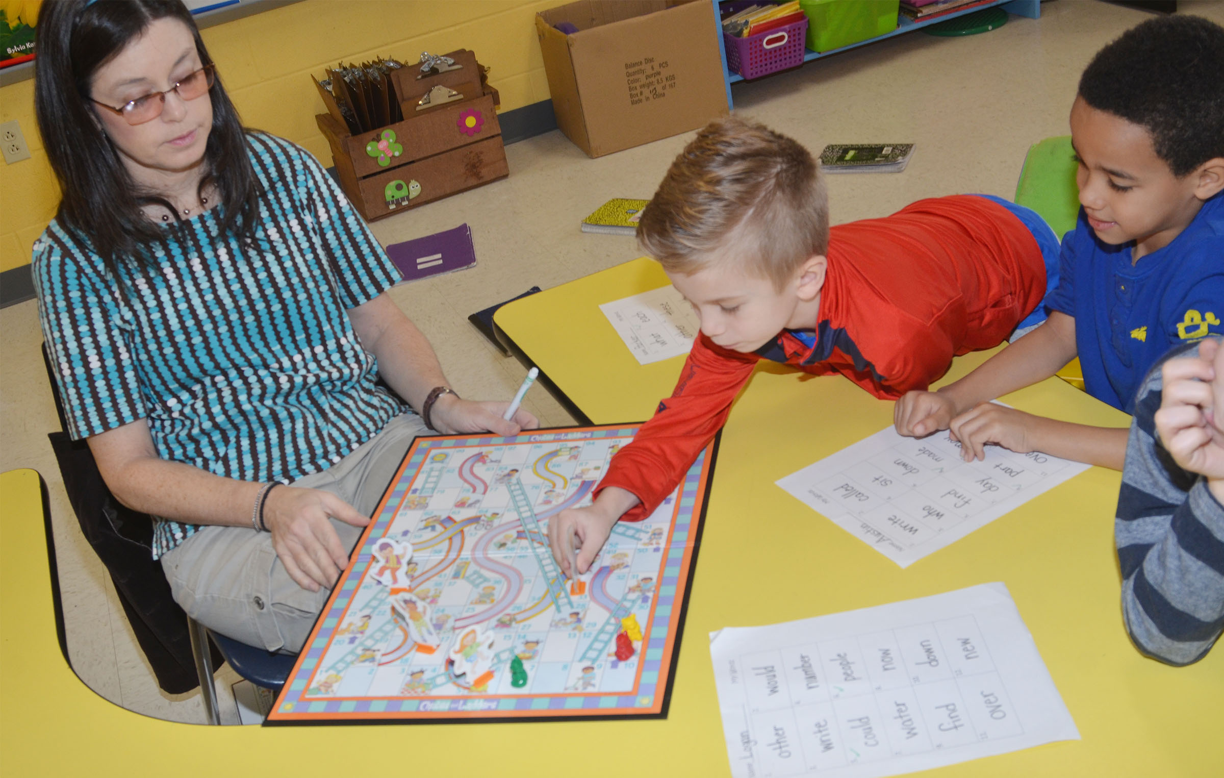 CES first-grade teacher Shirley Cox plays Candyland with students Parker Hamilton, at left, and Austin Hamilton to help them learn sight words.