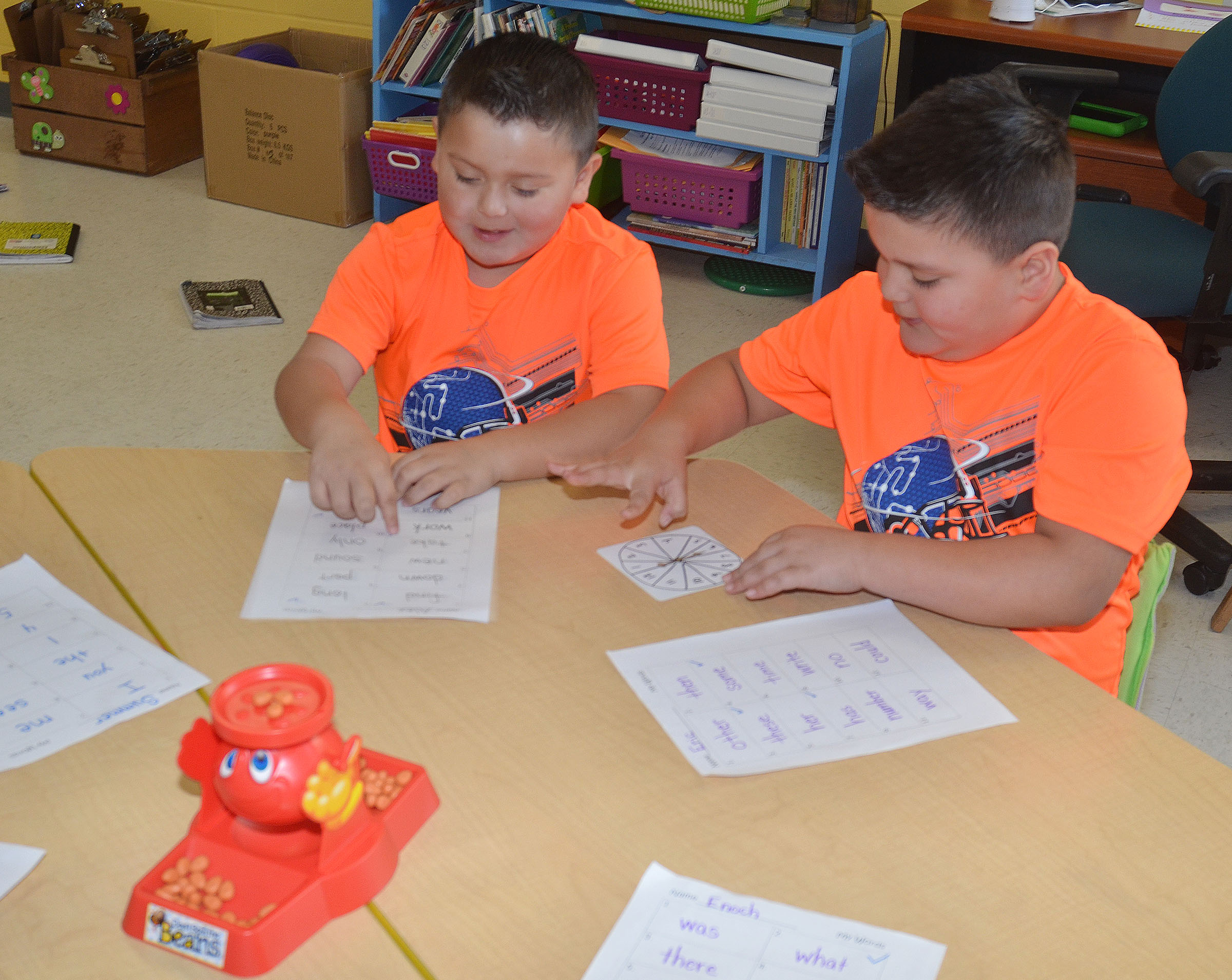 CES first-graders Alex Mixtega, at left, and his twin brother, Eric, practice pronouncing sight words while playing Don't Spill the Beans.