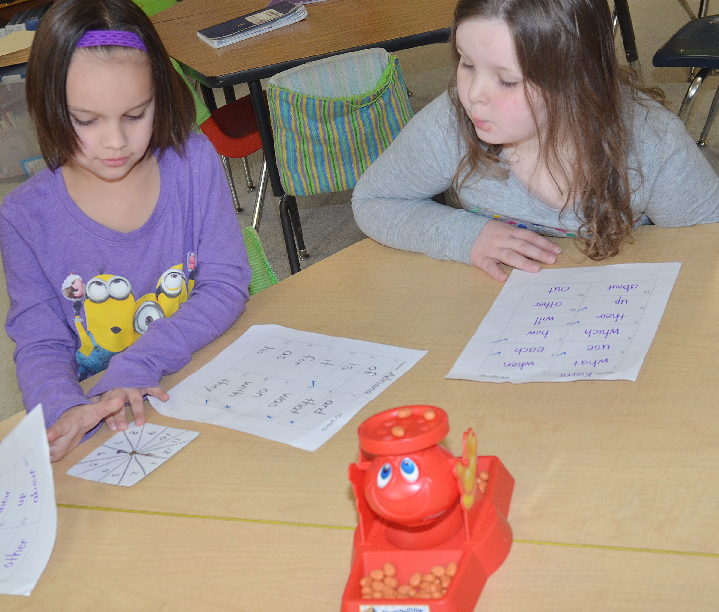 CES first-graders Adriana Agent, at left, and Kierra Maupin practice pronouncing sight words while playing Don't Spill the Beans.