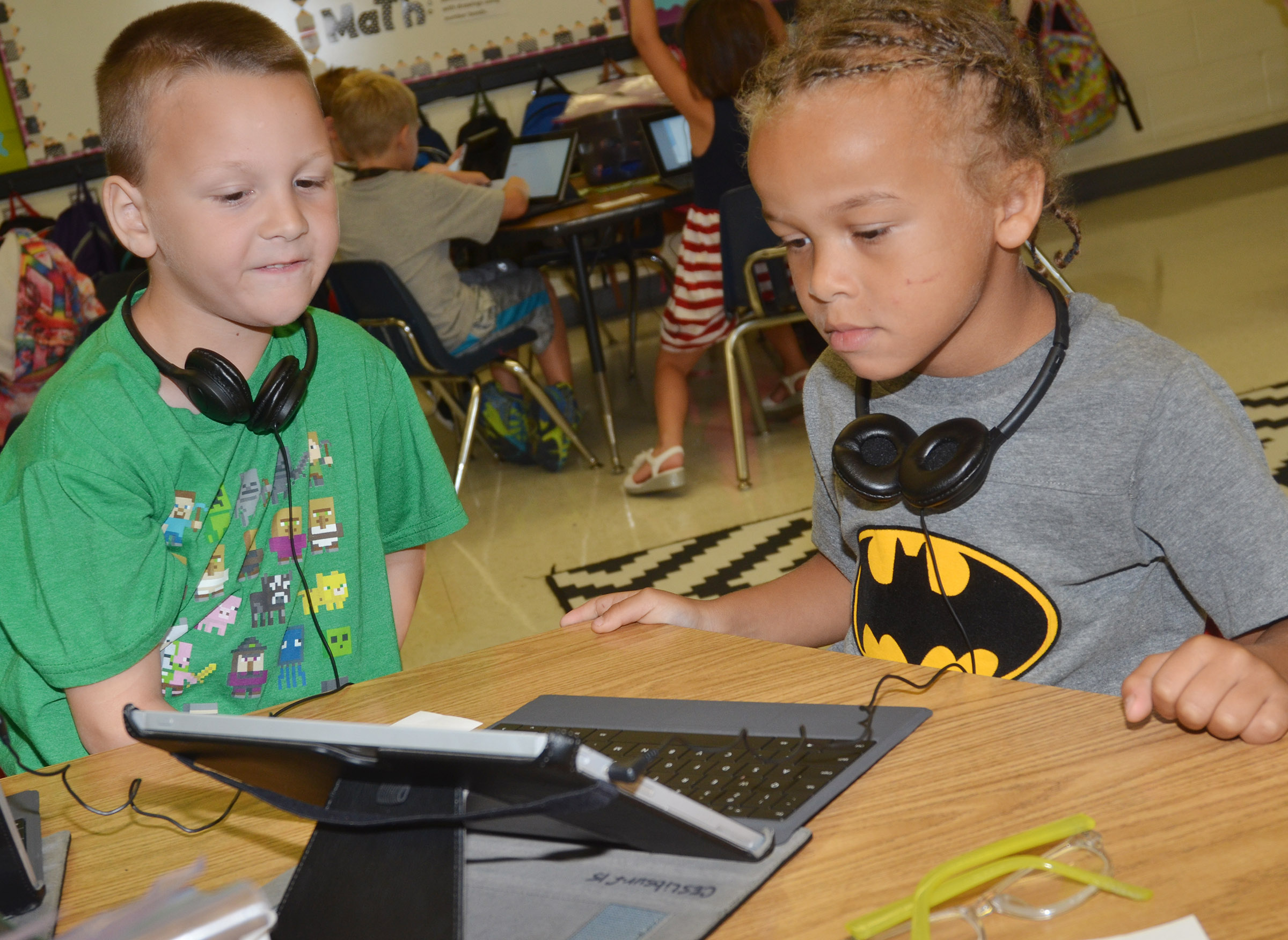 CES first-graders Justice Nelson, at left, and Dyra Welch log on to their tablets.