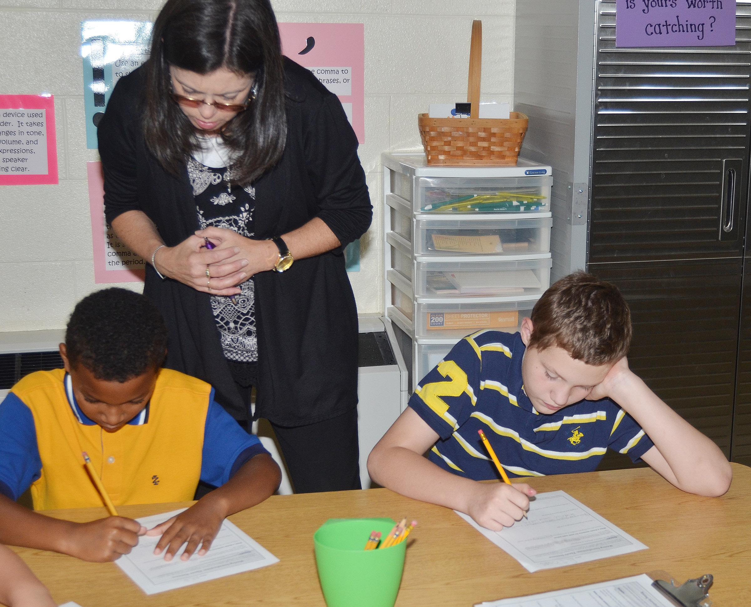 CES writing teacher Shirley Cox helps fifth-graders Javarius Gurley, at left, and Ethan Cox as they write thesis statements.