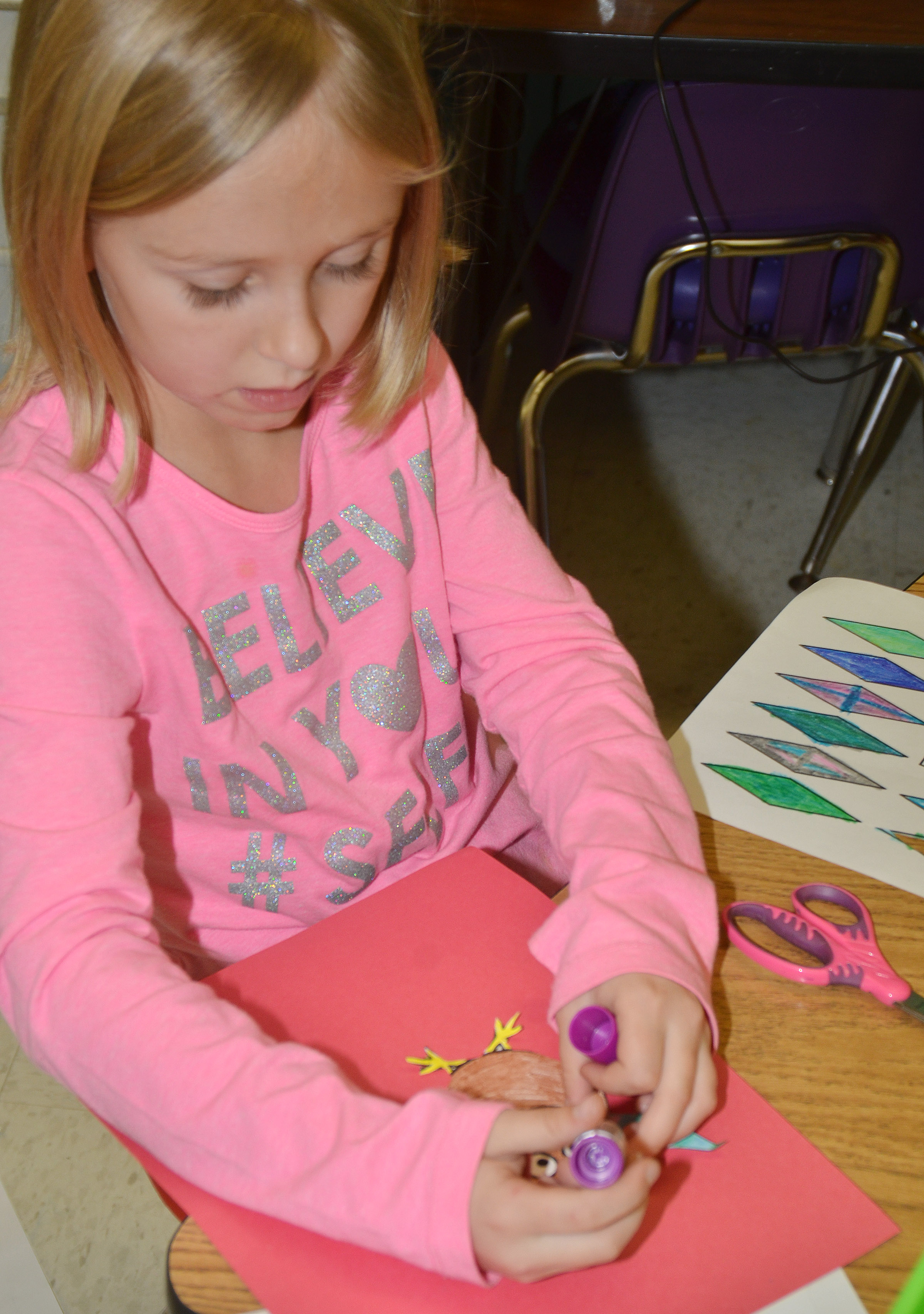 CES first-grader LeeAnna Garvin glues her turkey to construction paper.