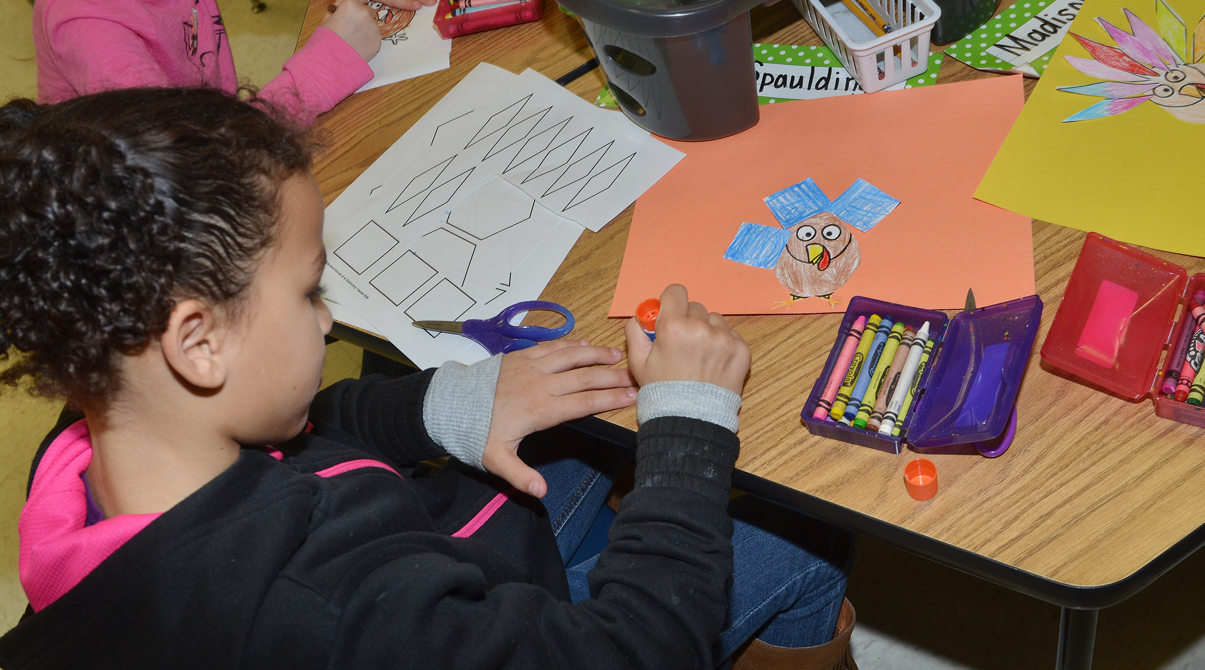 CES first-grader Aleeya Spaulding clues shapes together to create turkey feathers.