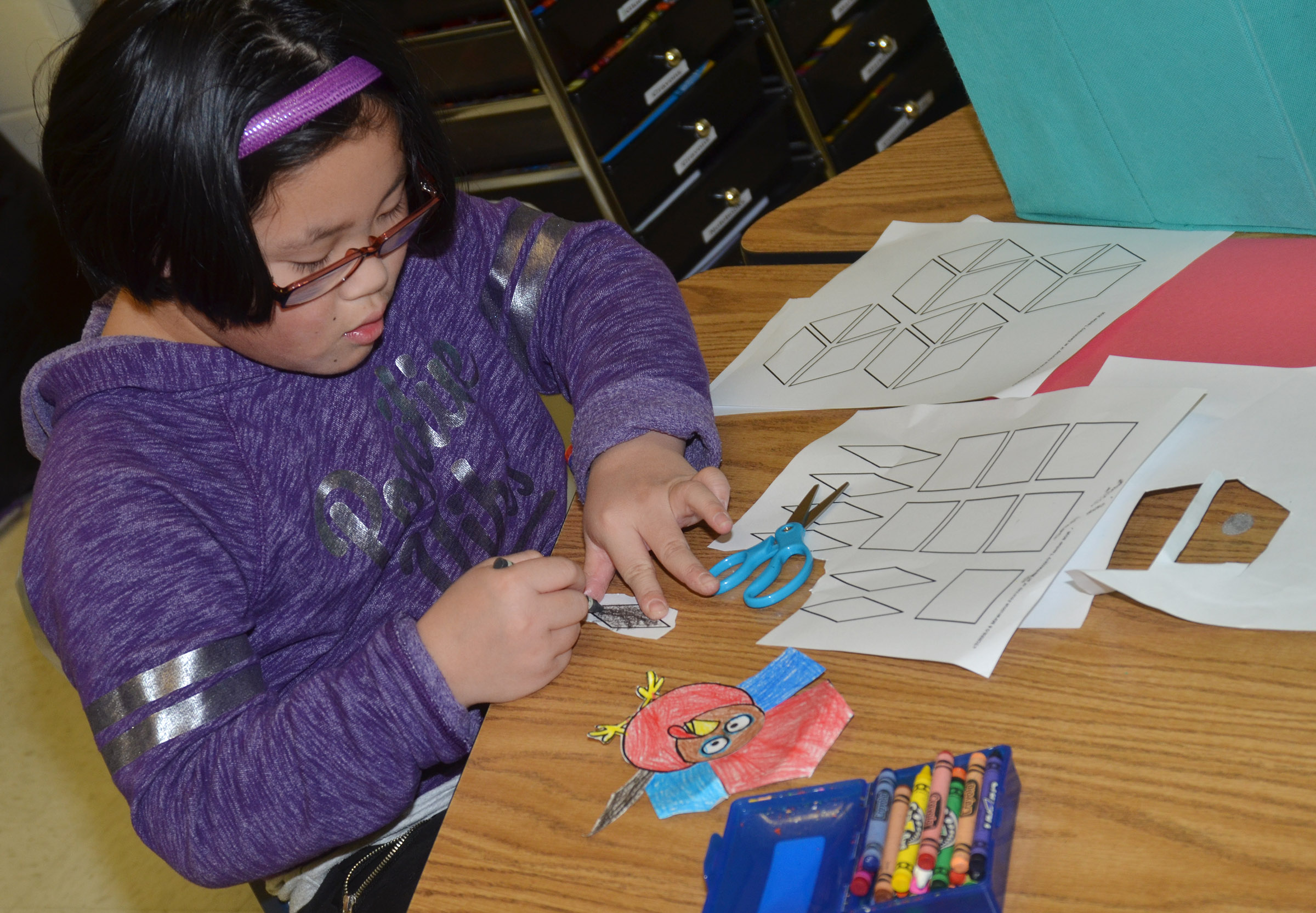 CES first-grader Vicky Li colors shapes to make her turkey feathers.