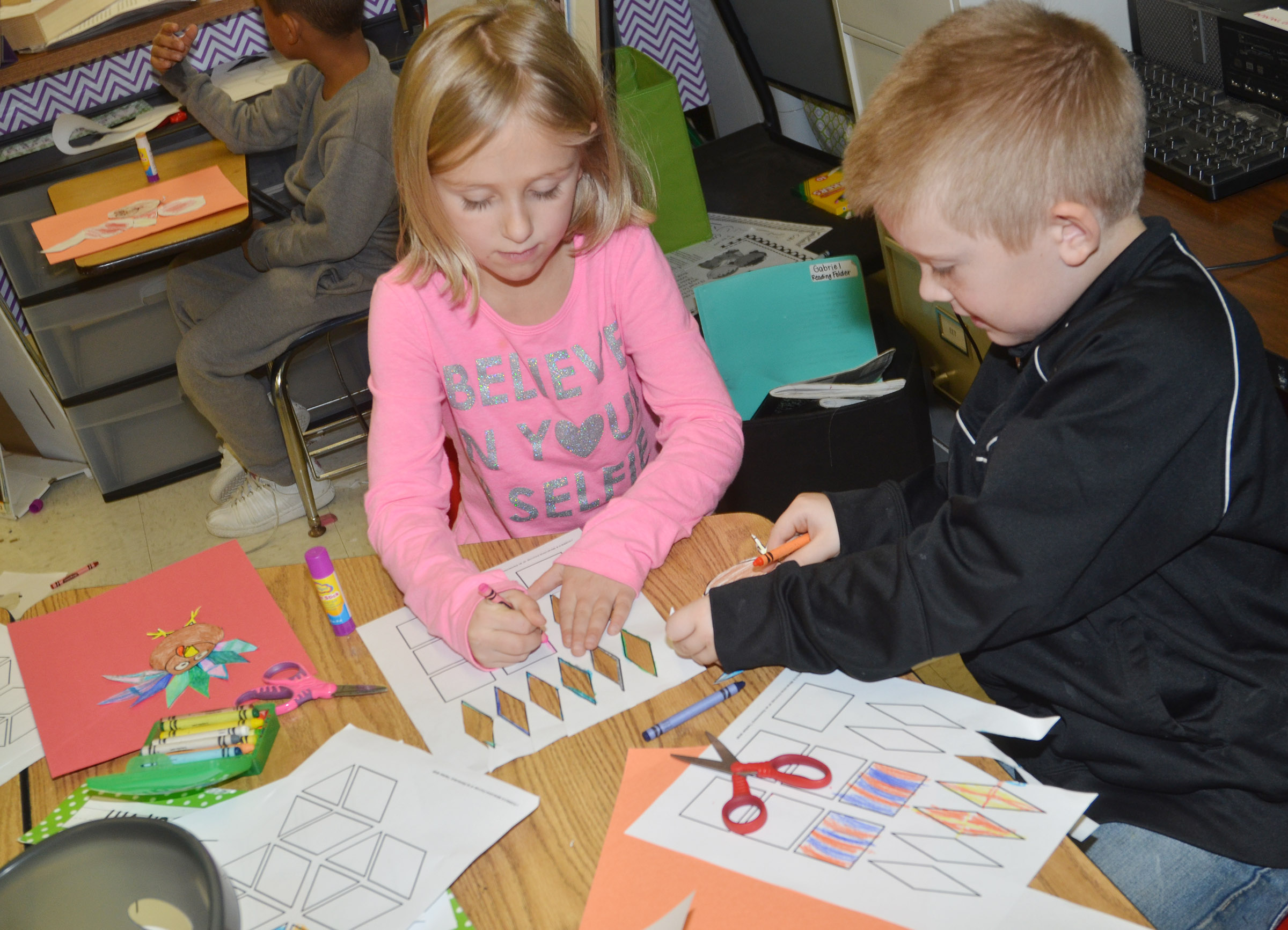 CES first-graders LeeAnna Garvin, at left, and Gage Henderson cut out and color shapes to make their turkey feathers.