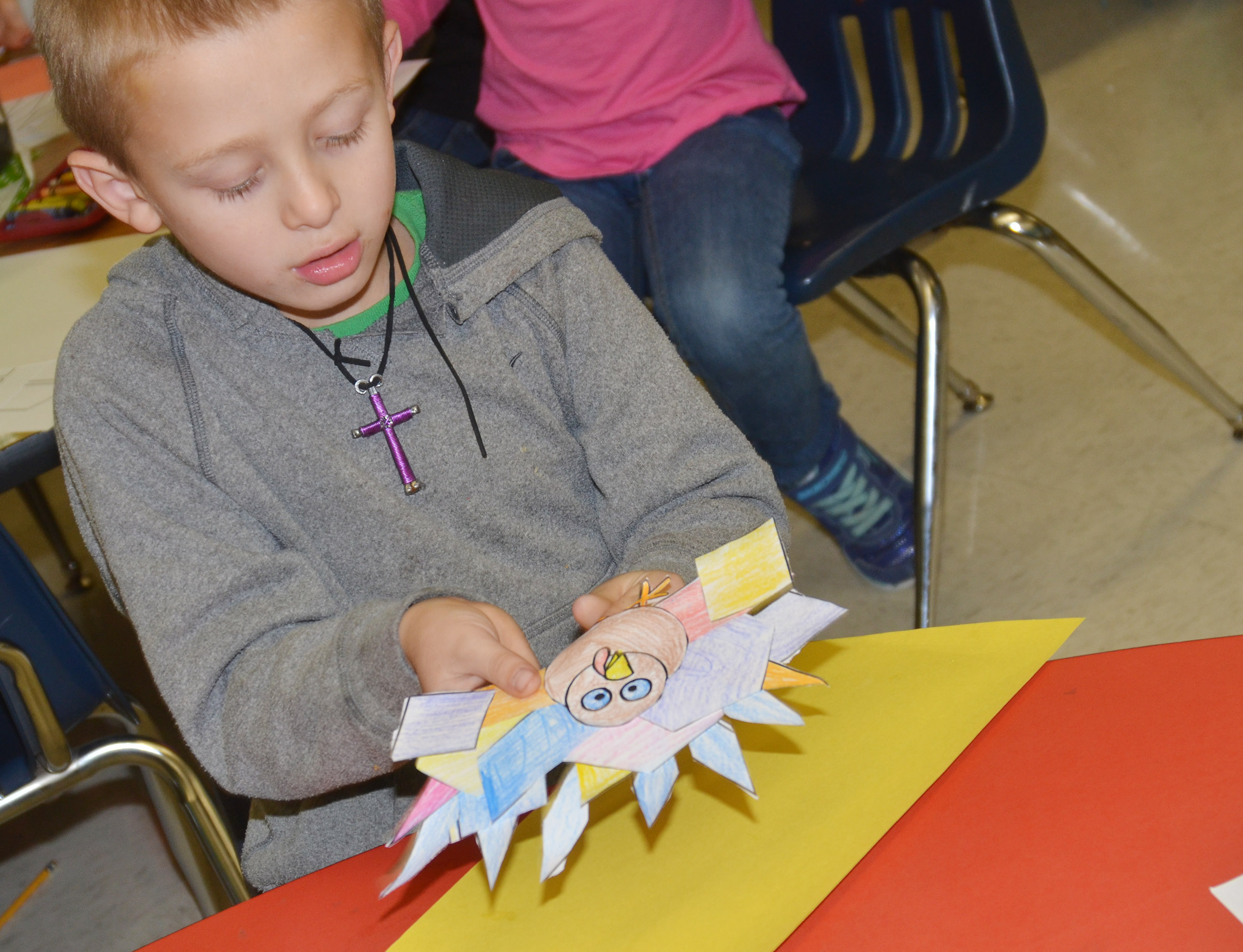CES first-grader Carson Brown glues his turkey to construction paper.