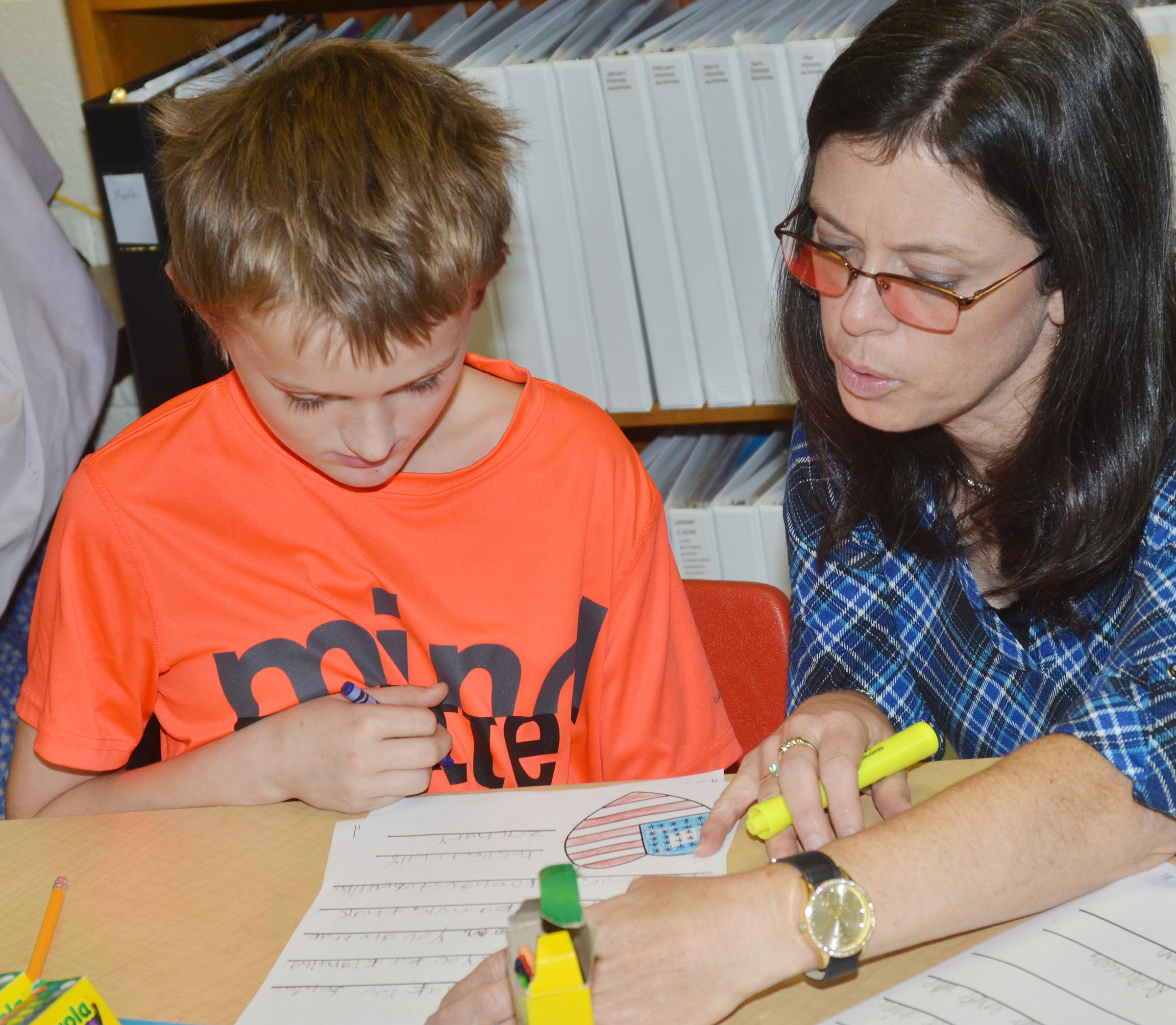 CES writing teacher Shirley Cox helps third-grader Zachary Cox as he writes a letter to a veteran.
