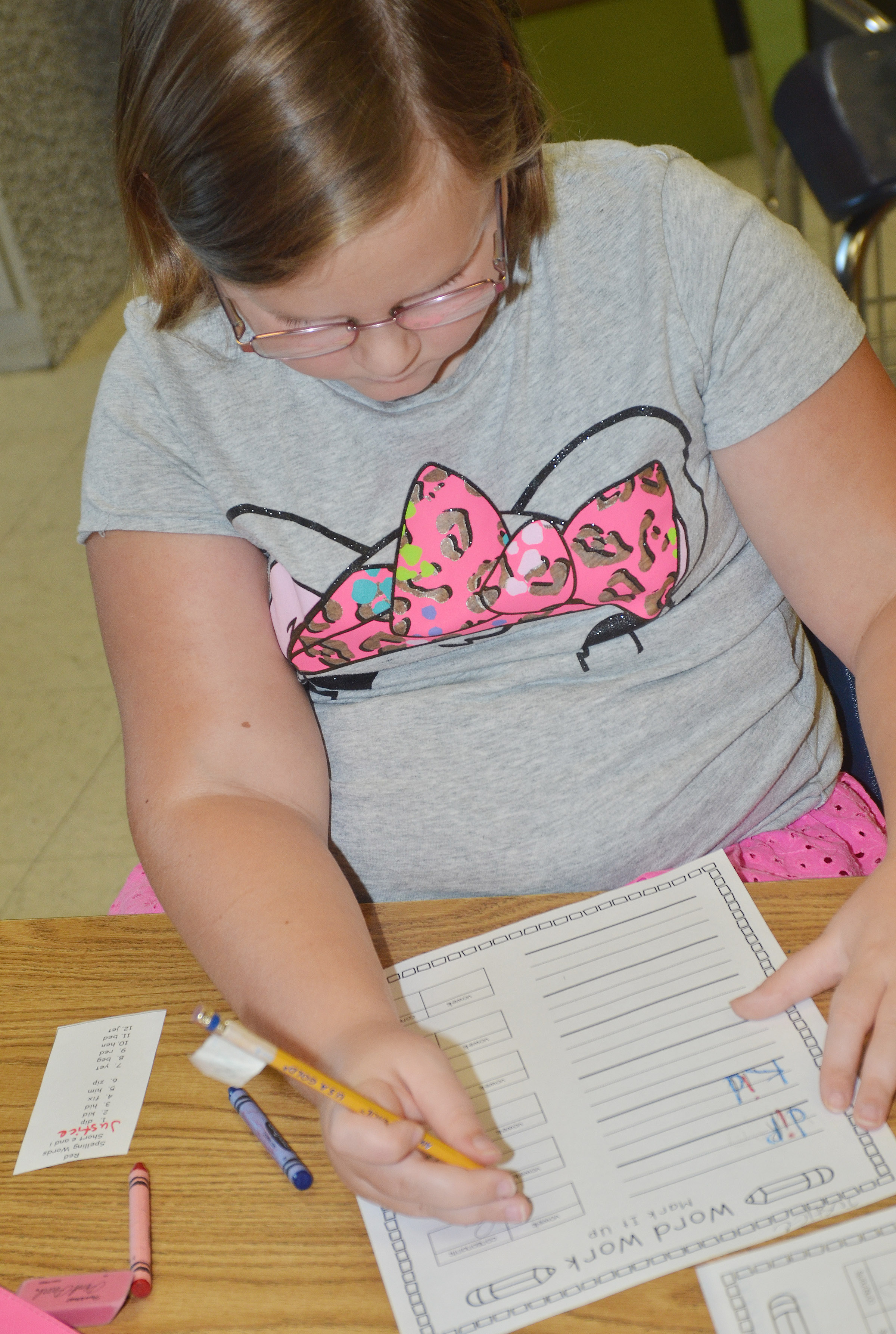 CES second-grader Justice Albrecht writes a vocabulary word, using one color for the consonants and another for the vowels.