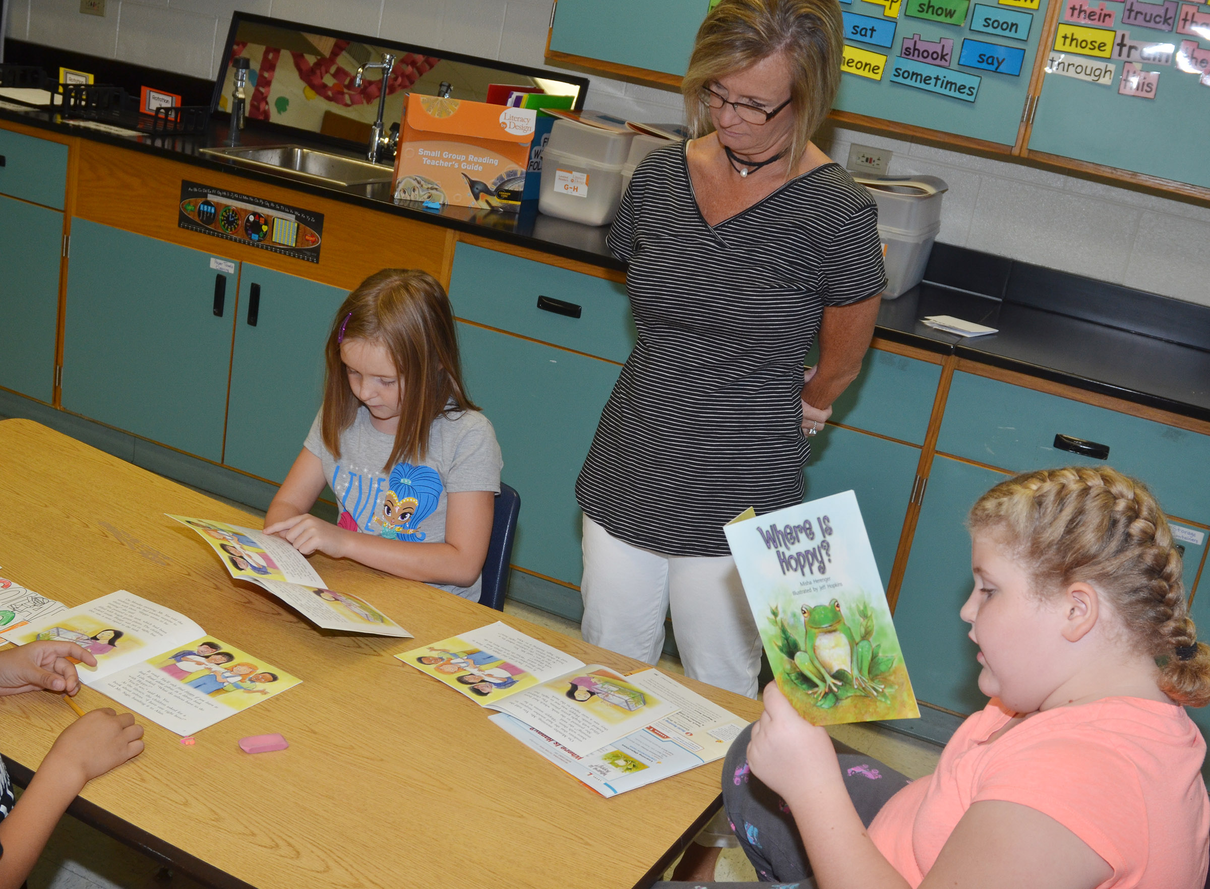 CES second-graders Gracie Murphy, at left, and Elizabeth Foster read with teacher Melanie Cox.
