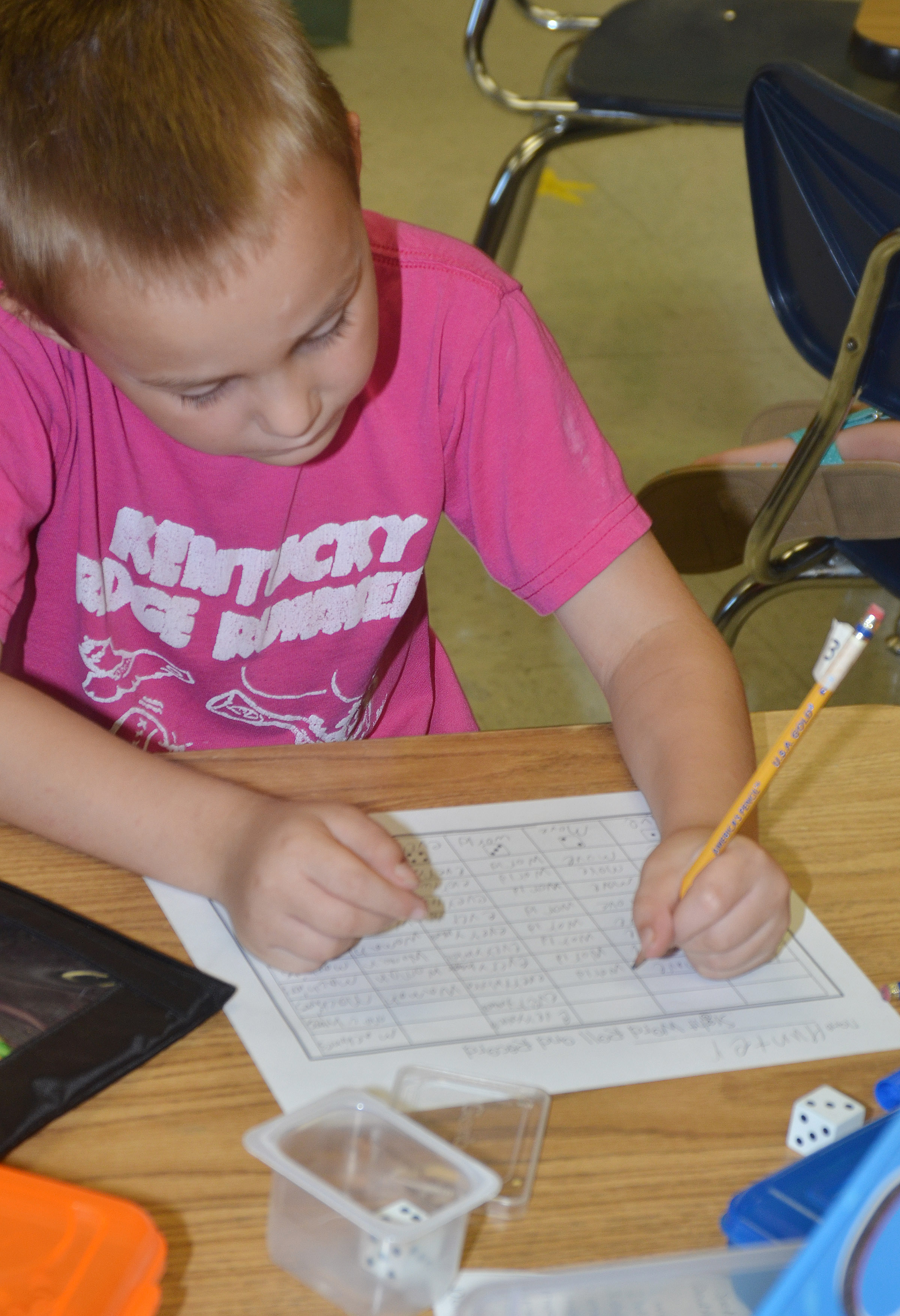 CES second-grader Hunter Bates writes his vocabulary words after rolling his dice.