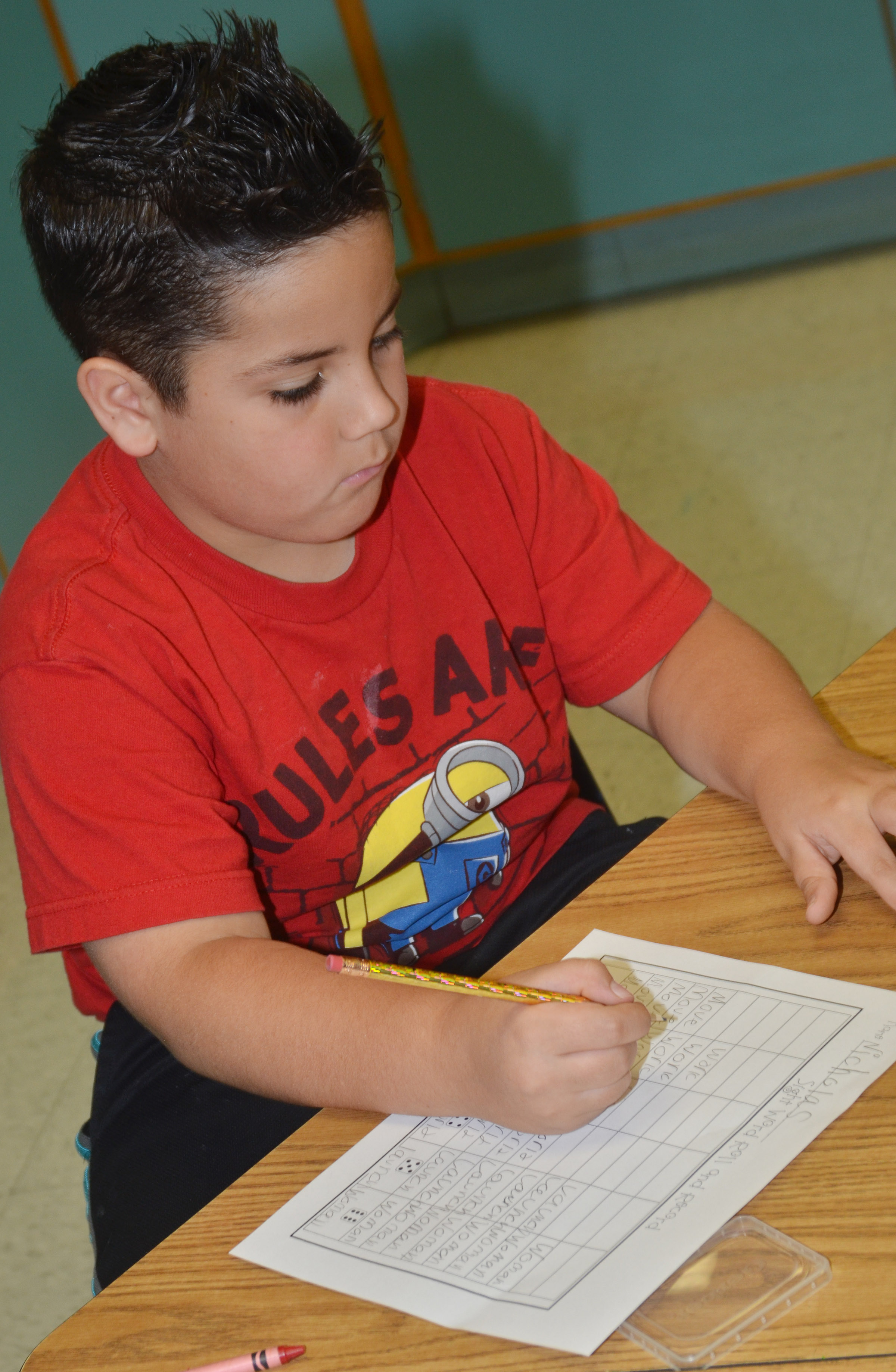 CES second-grader Nicholas Almeida writes his vocabulary words after rolling his dice.