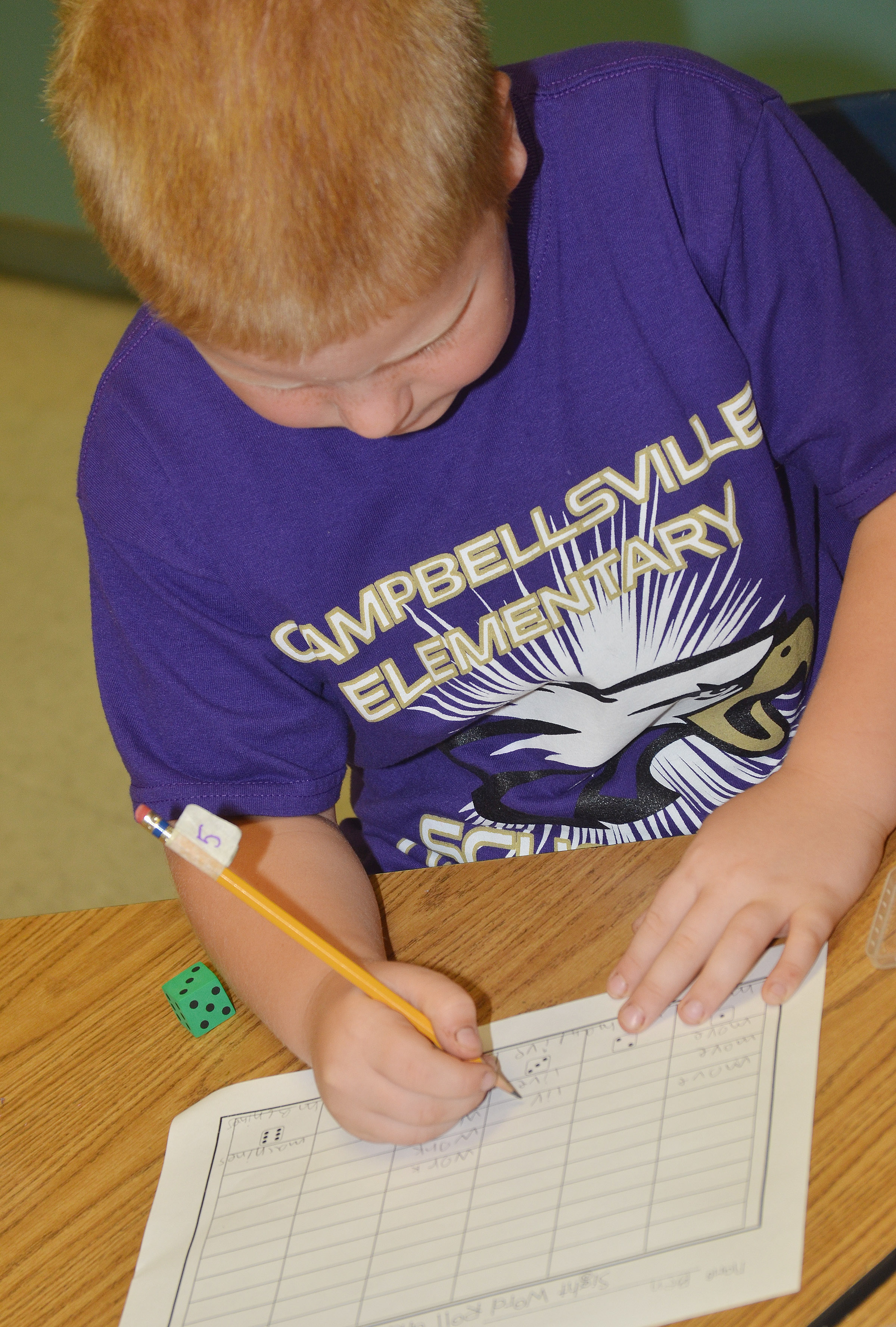 CES second-grader Ben Parrott writes his vocabulary words after rolling his dice.