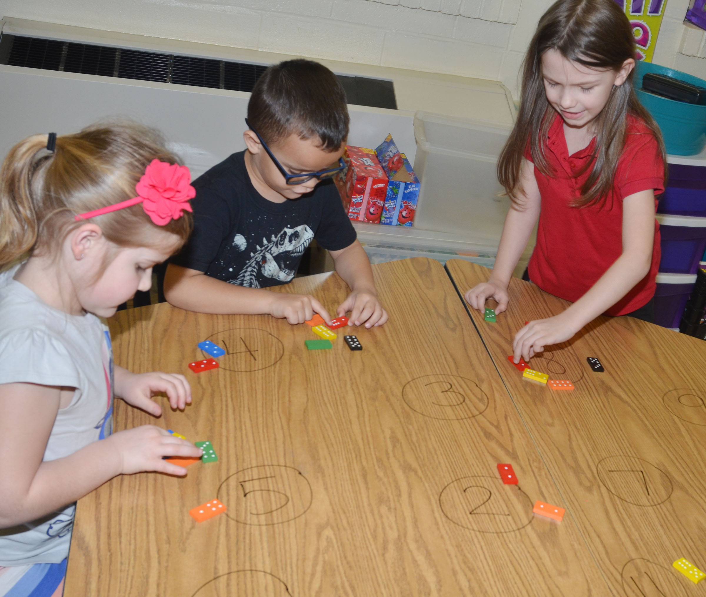 CES kindergarteners, from left, Aubreigh Knifley, Davian Taylor and Melody Ward match the dots on Dominos to numbers written on their desk.