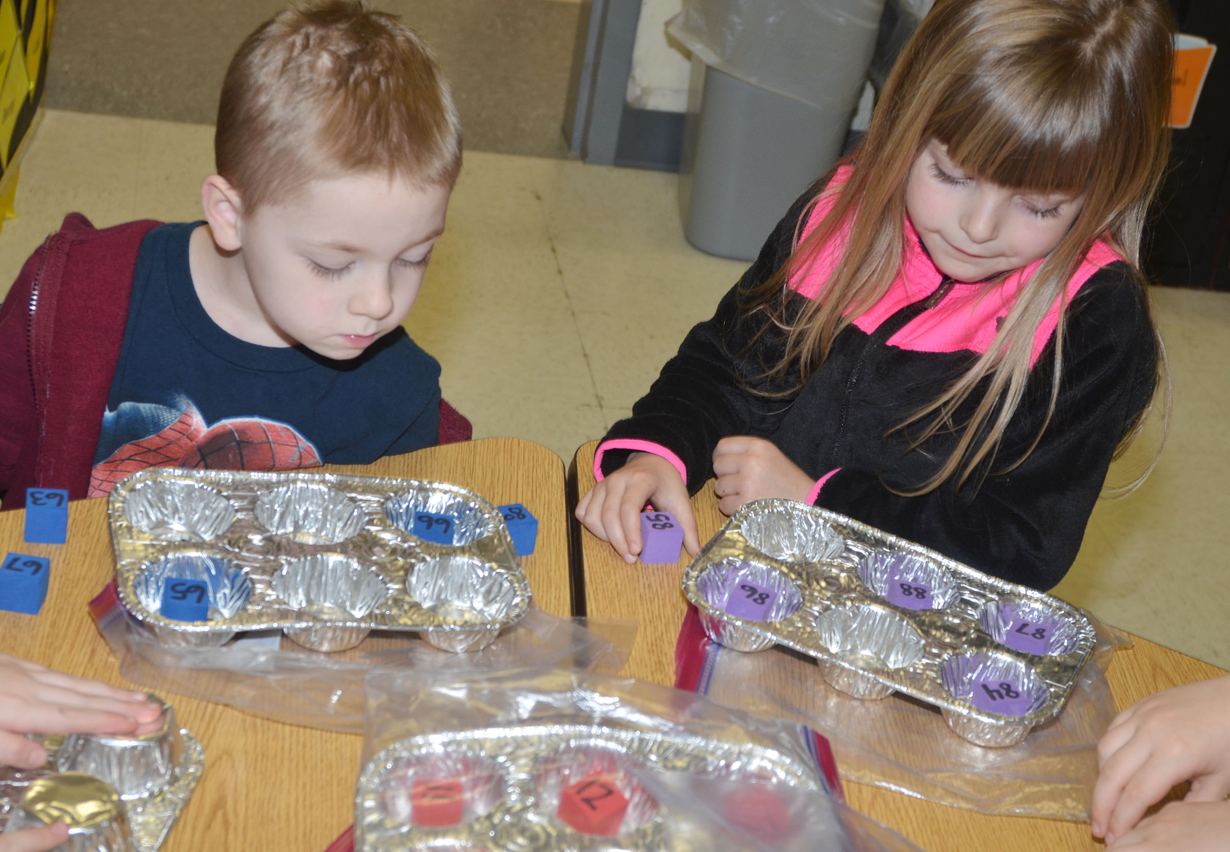 CES kindergarteners Noah Milburn, at left, and Madison Wilhoite put the numbers on their blocks in order.