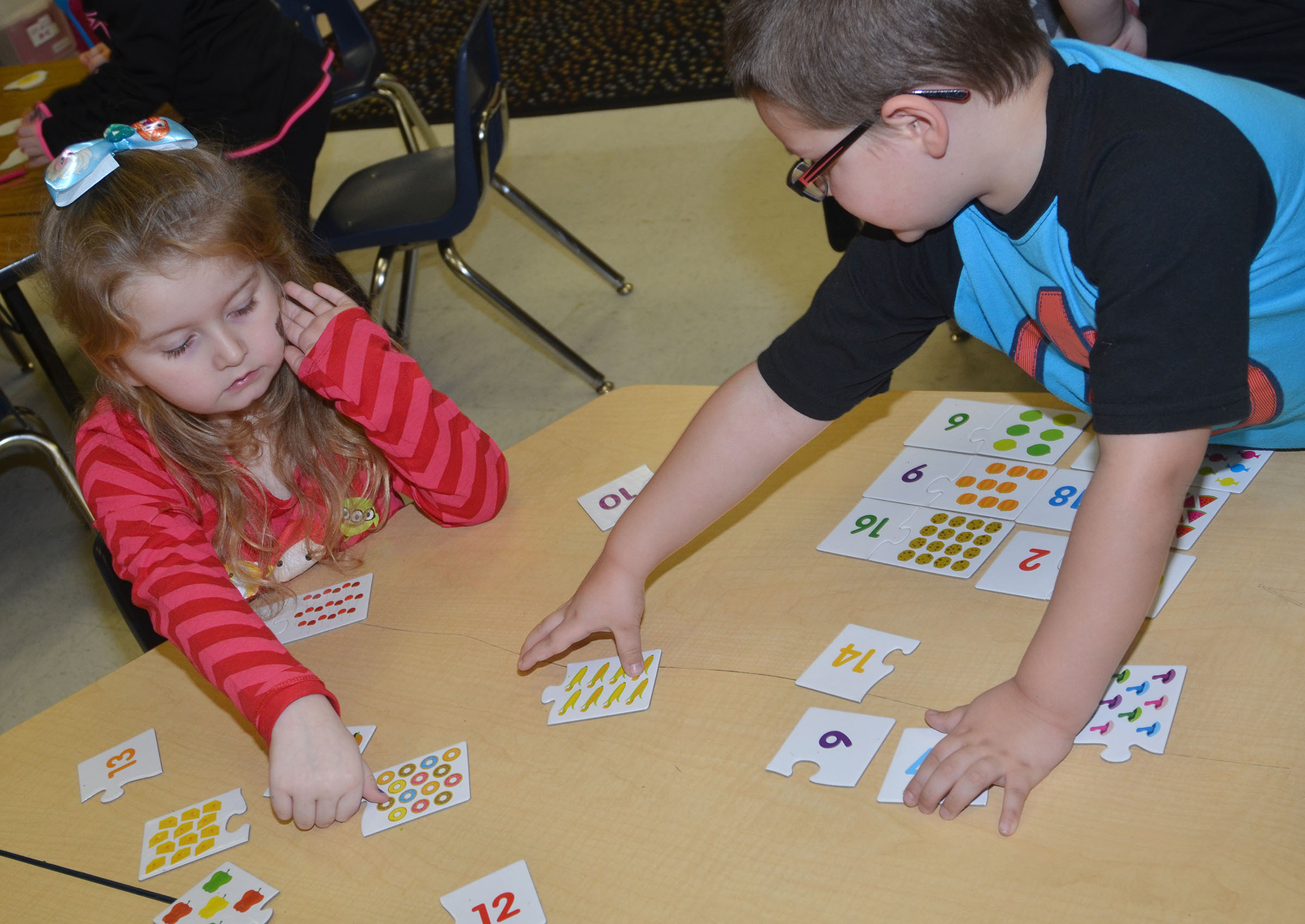 CES kindergarteners Laurna McKenzie, at left, and Tristan Burton count objects and then find the card with the correct number of objects.
