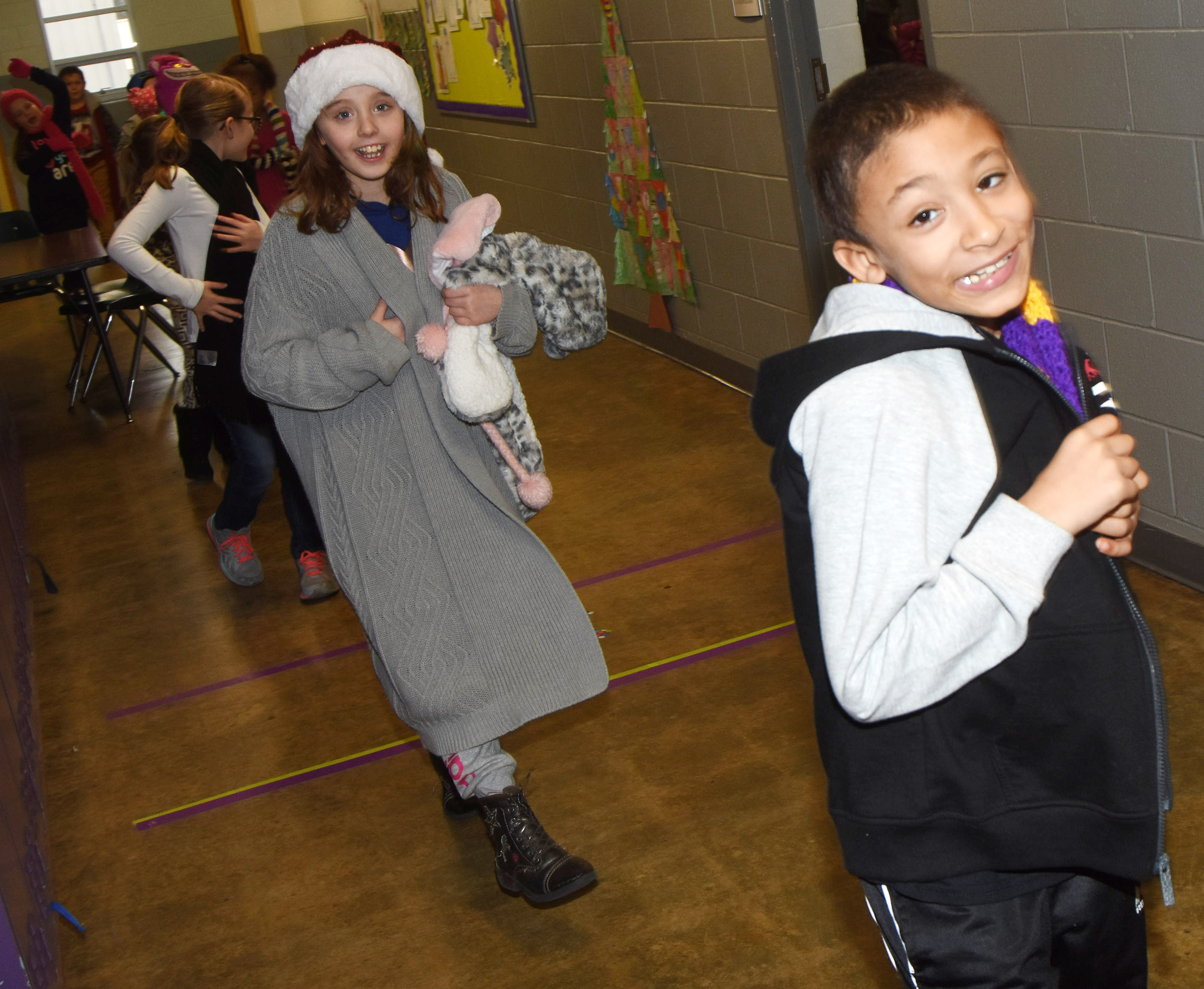 CES second-graders Kiley Noble, at left, and Eli Williams sing Christmas carols as they walk through the CES hallways.