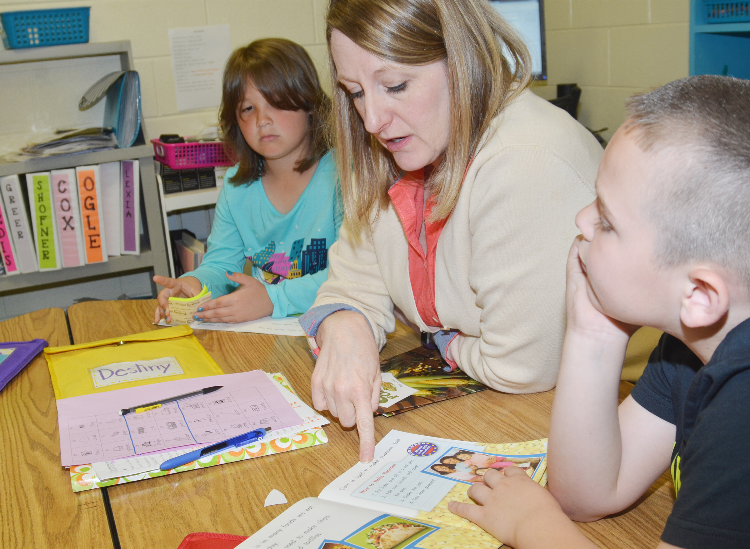 CES teacher Laura Dicken reads with first-graders Destiny Rhinehart, at left, and Colton Maggard.