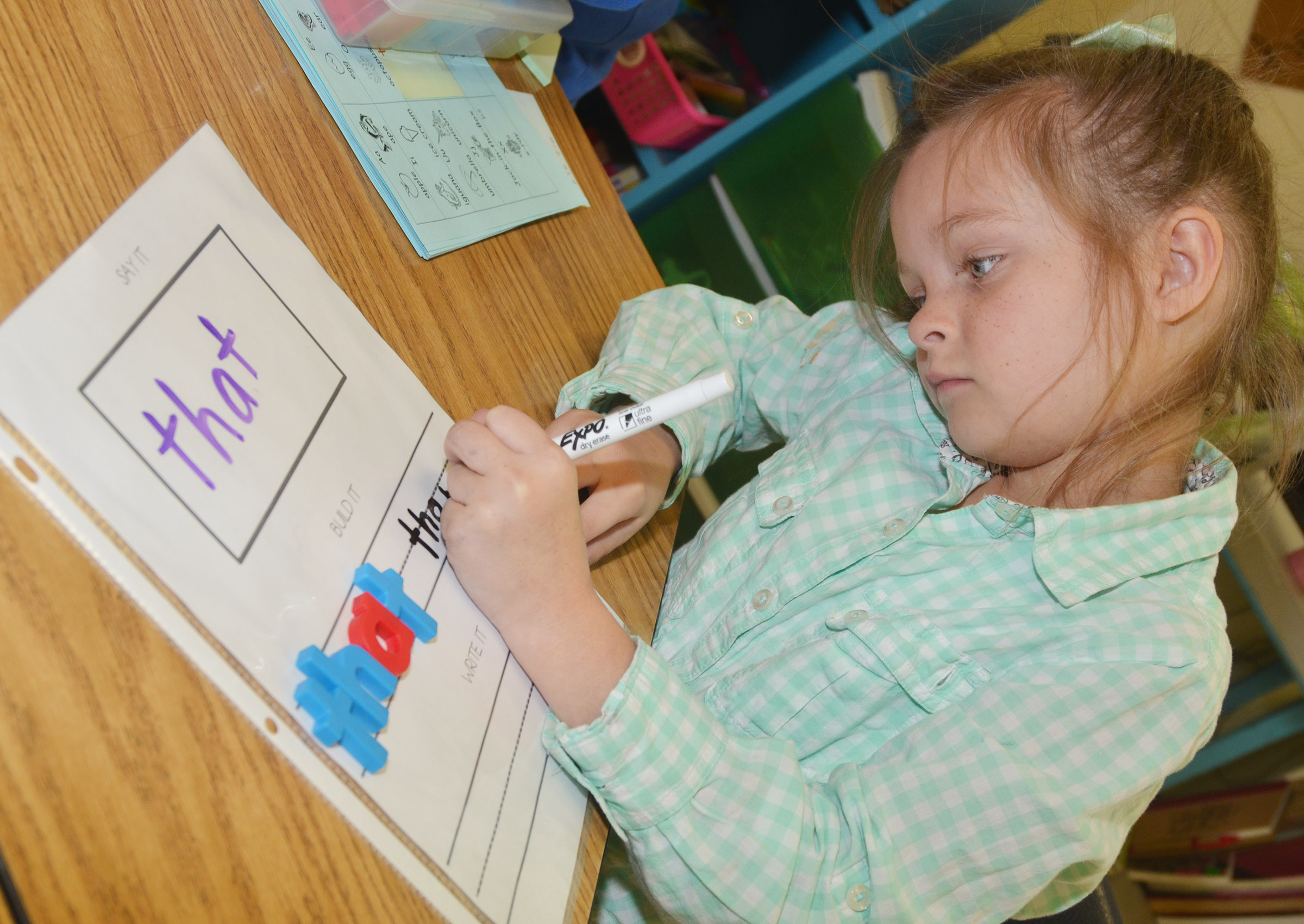 "CES first-grader Addison Perkins writes the word ""that."""
