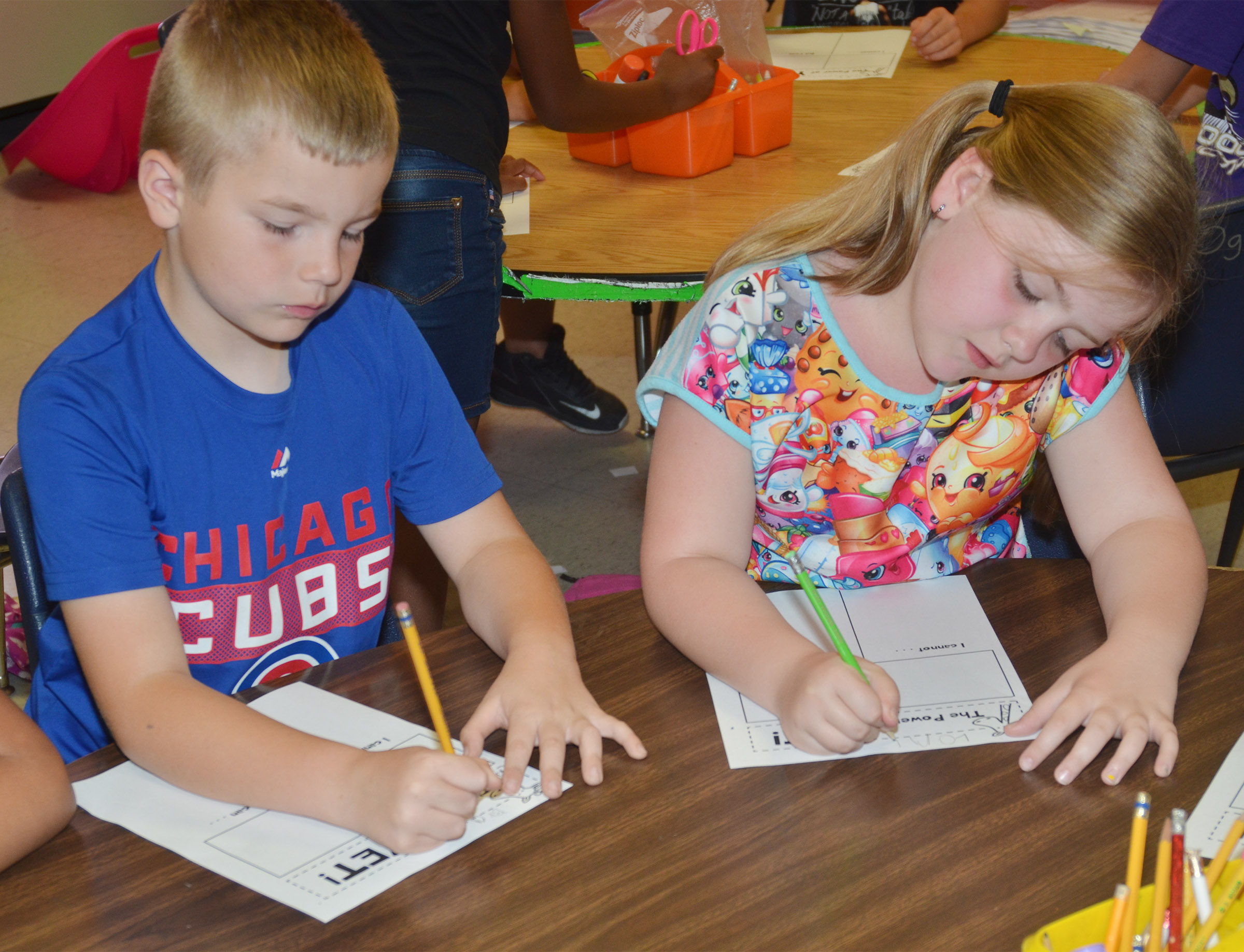 CES first-graders Brady Cox, at left, and London Whitlow write about something they can do now, but also something they can't just yet.