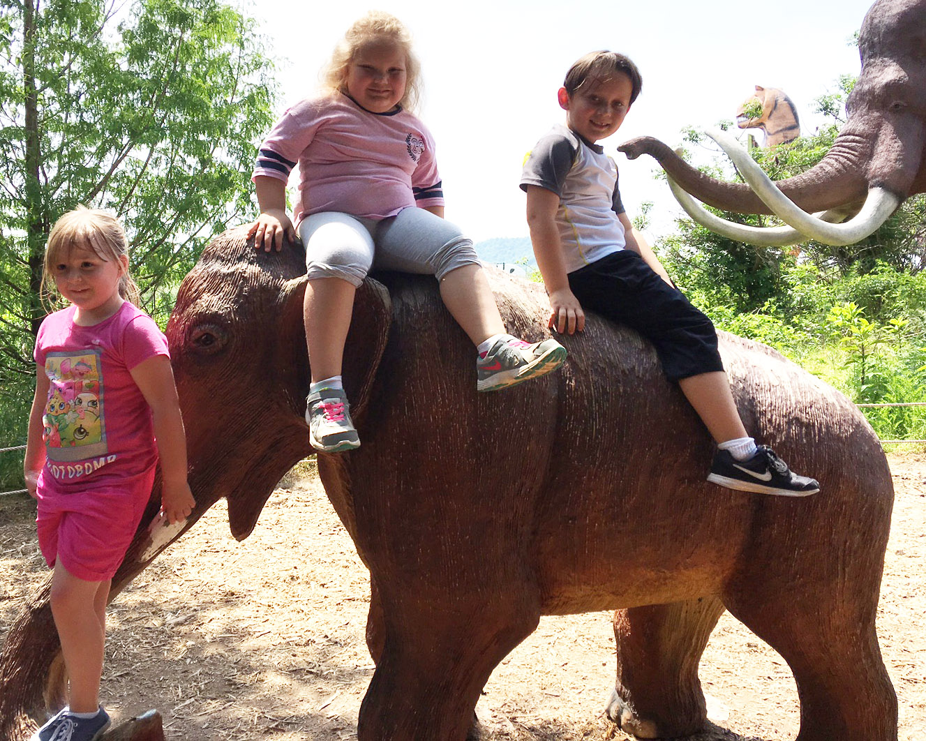 From left, CES kindergarteners Briley Sapp, ReAnna Jeffries and Karter Young sit on a dinosaur.