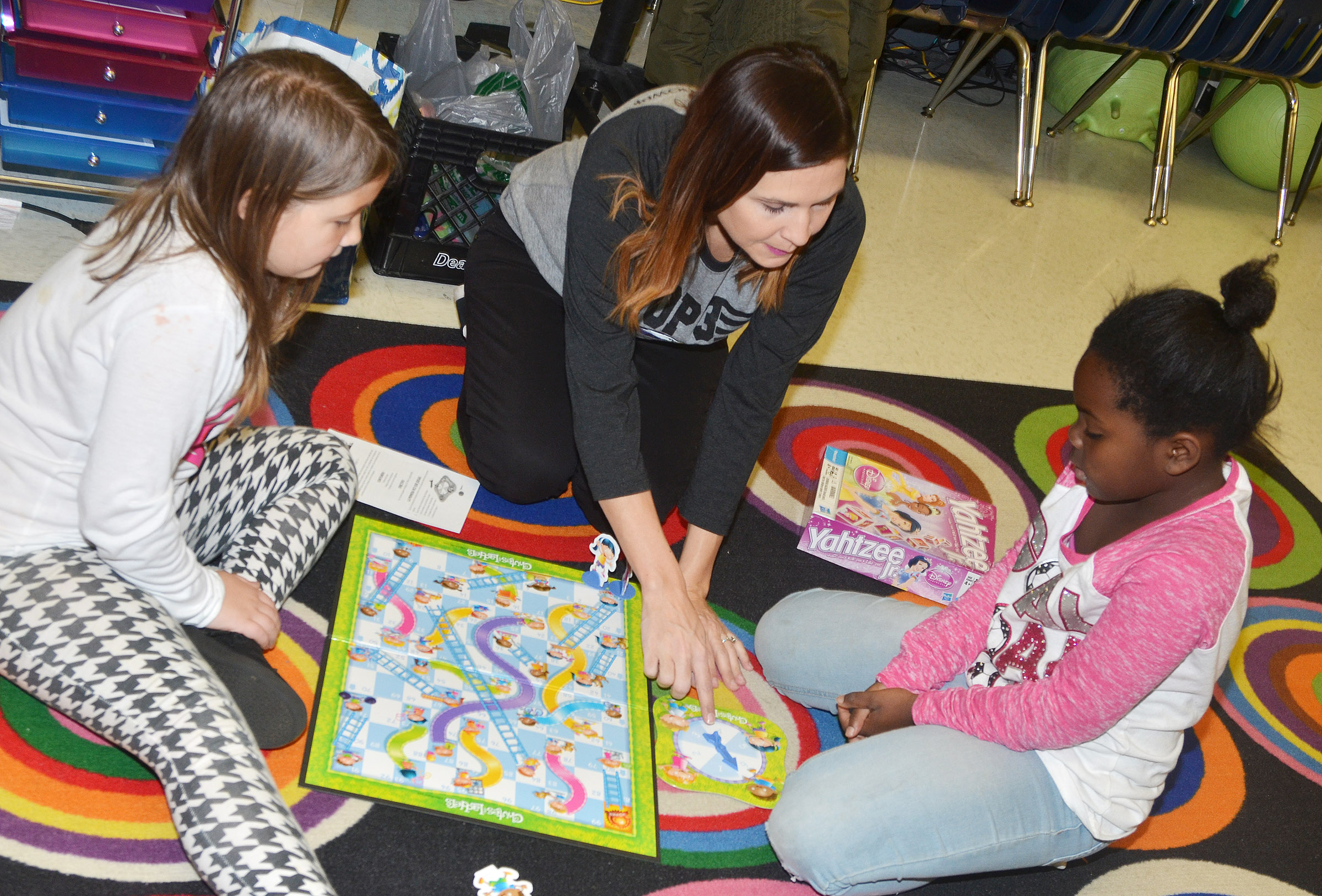 CES first-grade teacher Luci Shofner plays Chutes and Ladders with Destiny Rhinehart, at left, and Aniyah Adams.