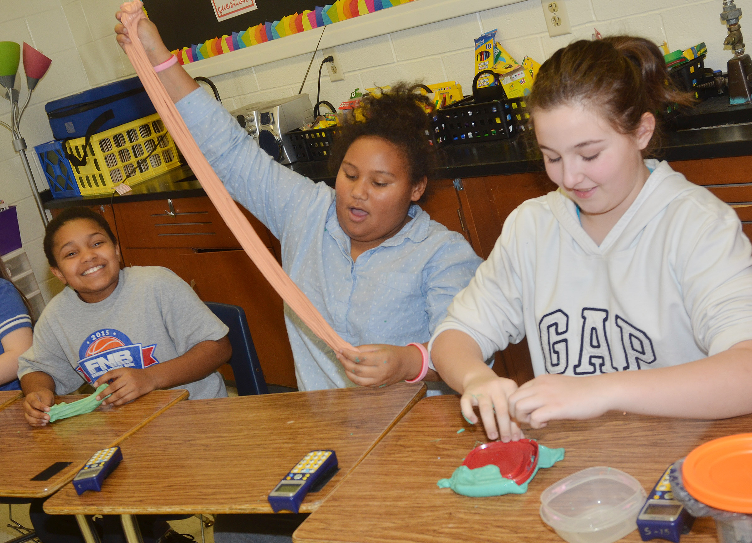 CES fifth-graders, from left, Jaclyn Jackson, Dezarae Washington and Riley Newton play with slime.