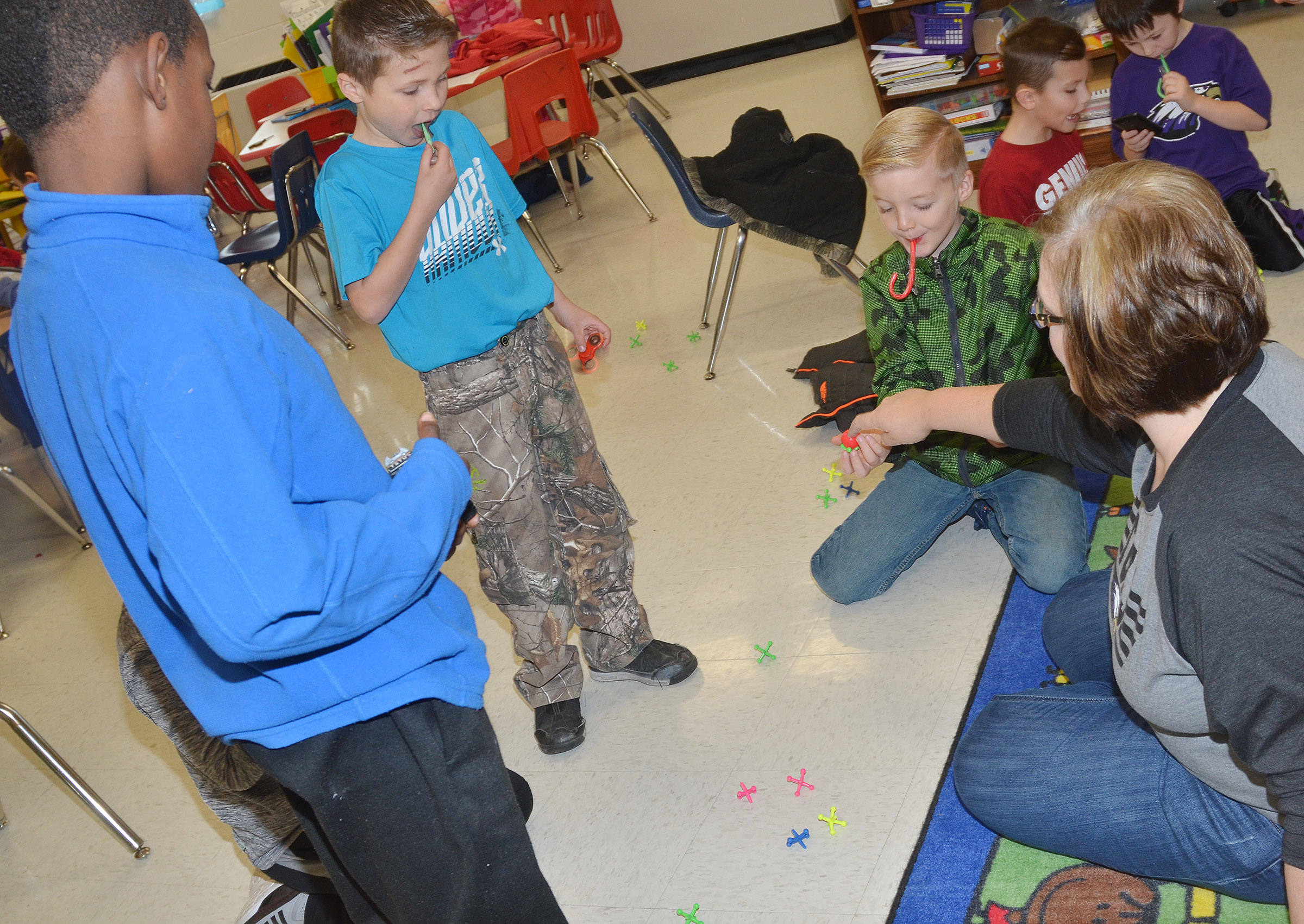 CES second-grade teacher Tonya Hagan plays Jacks with her students. From left are Lazarick Miller, Bryson Gabehart and Parker Scharbrough.