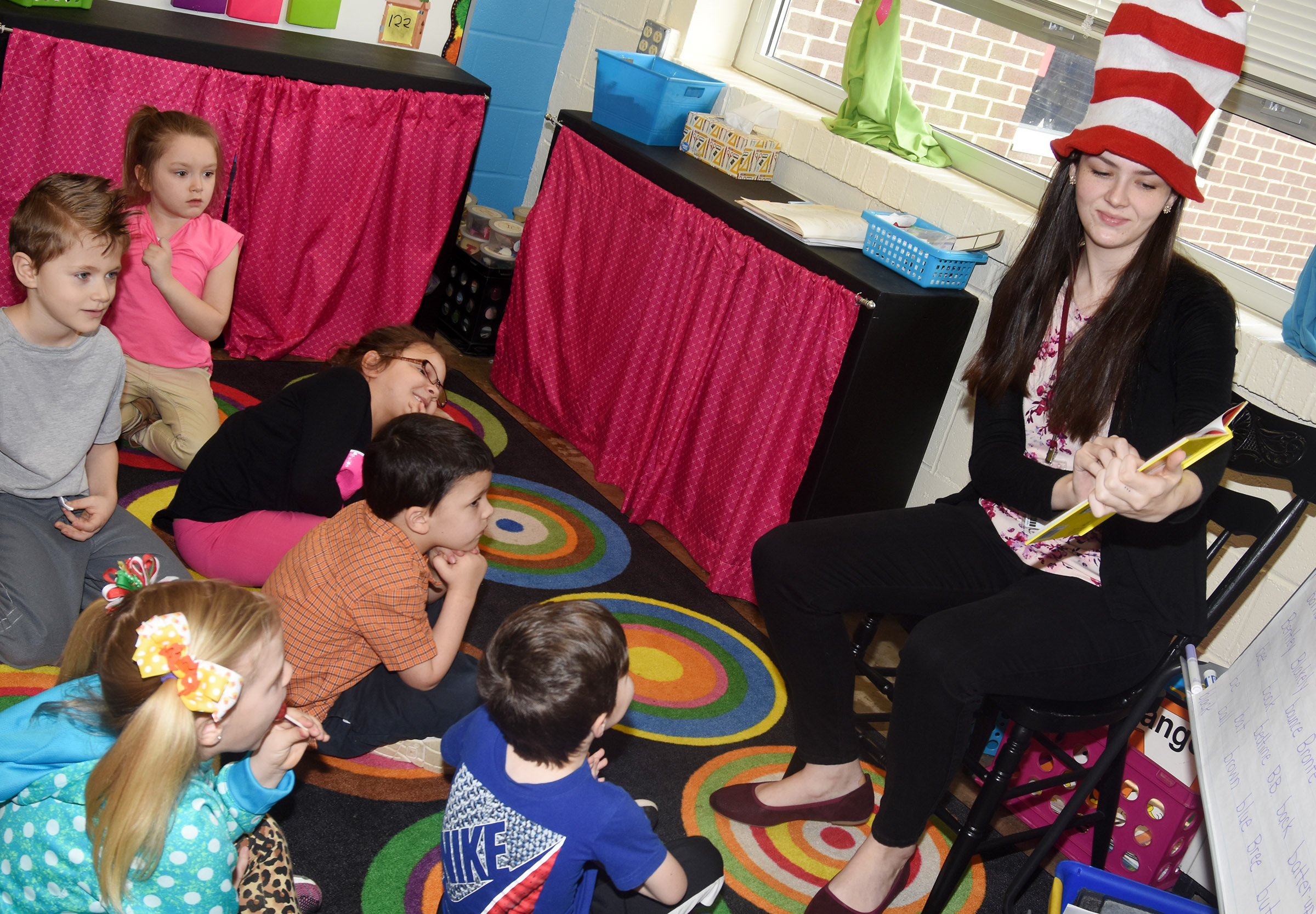 CU education student Emily Ford reads a Dr. Seuss book to CES kindergarten students.