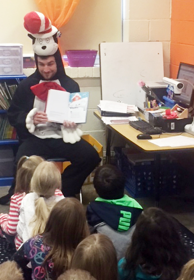 CU education student David Sparks reads a Dr. Seuss book to CES kindergarten students.