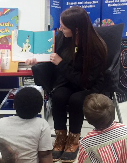 CU education student Kaitlyn Farmer reads a Dr. Seuss book to CES kindergarten students.