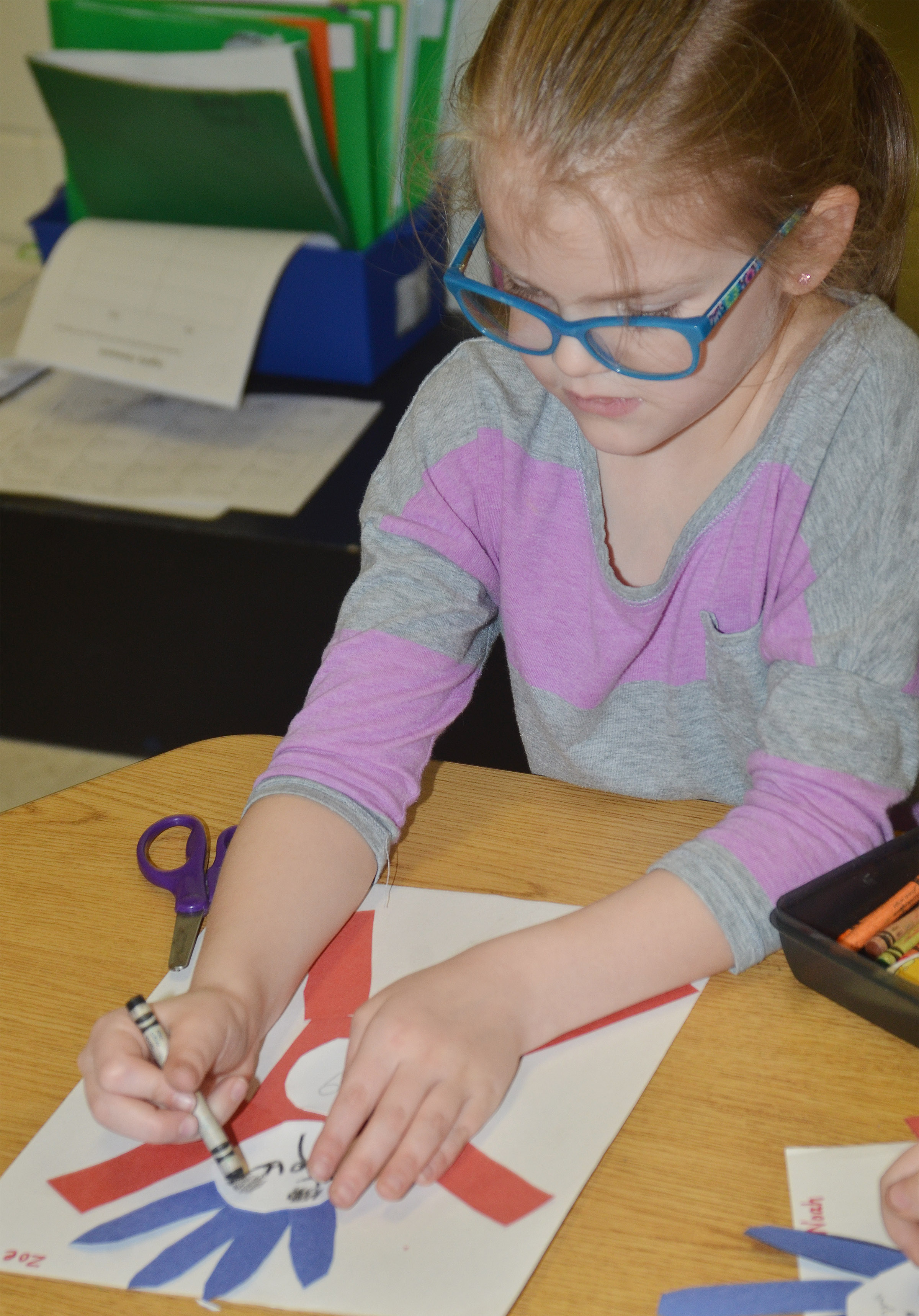 CES kindergartener Zoe Weddle draws a face on his Thing 1 character.