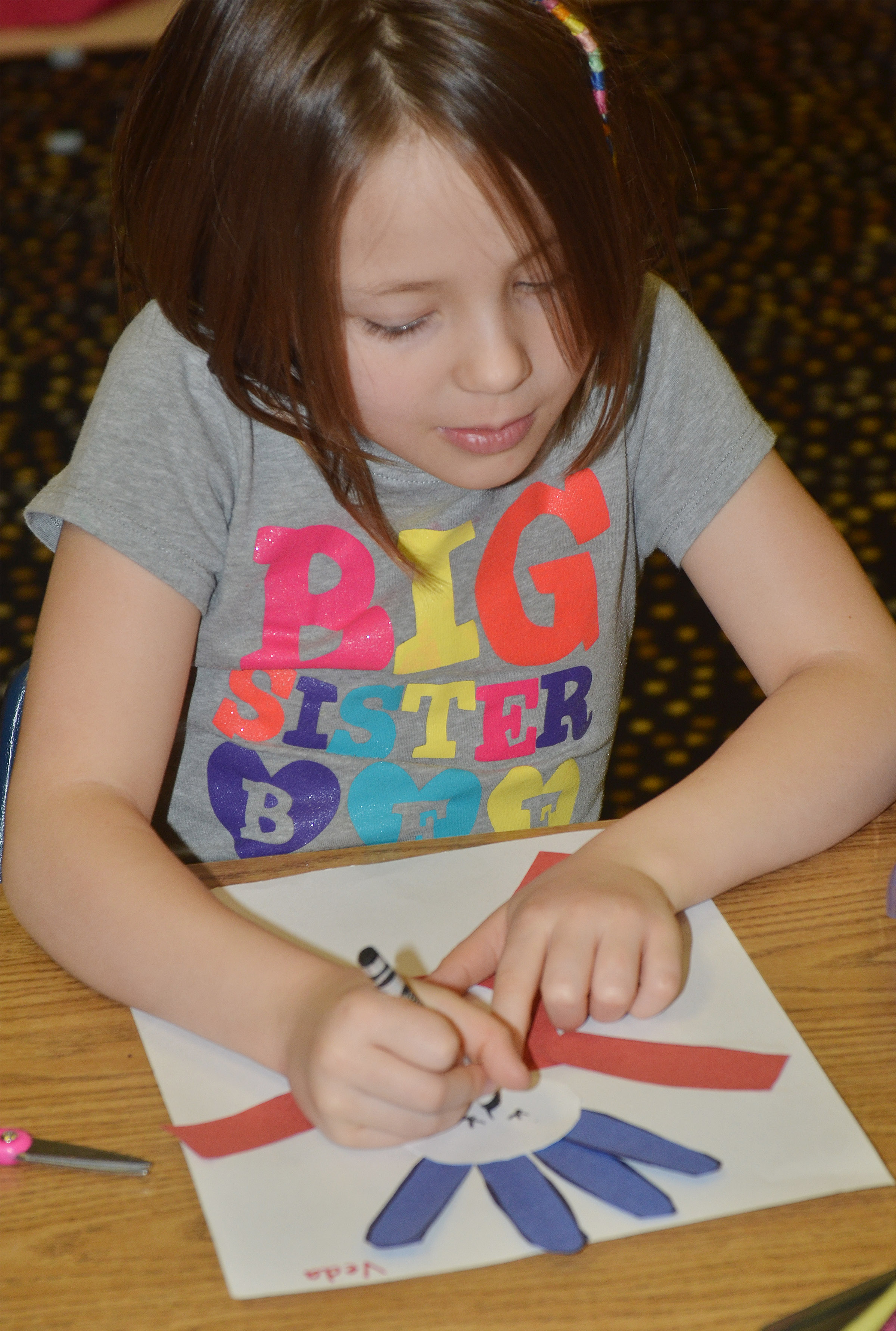 CES kindergartener Veda Burgess draws a face on her Thing 1 character.