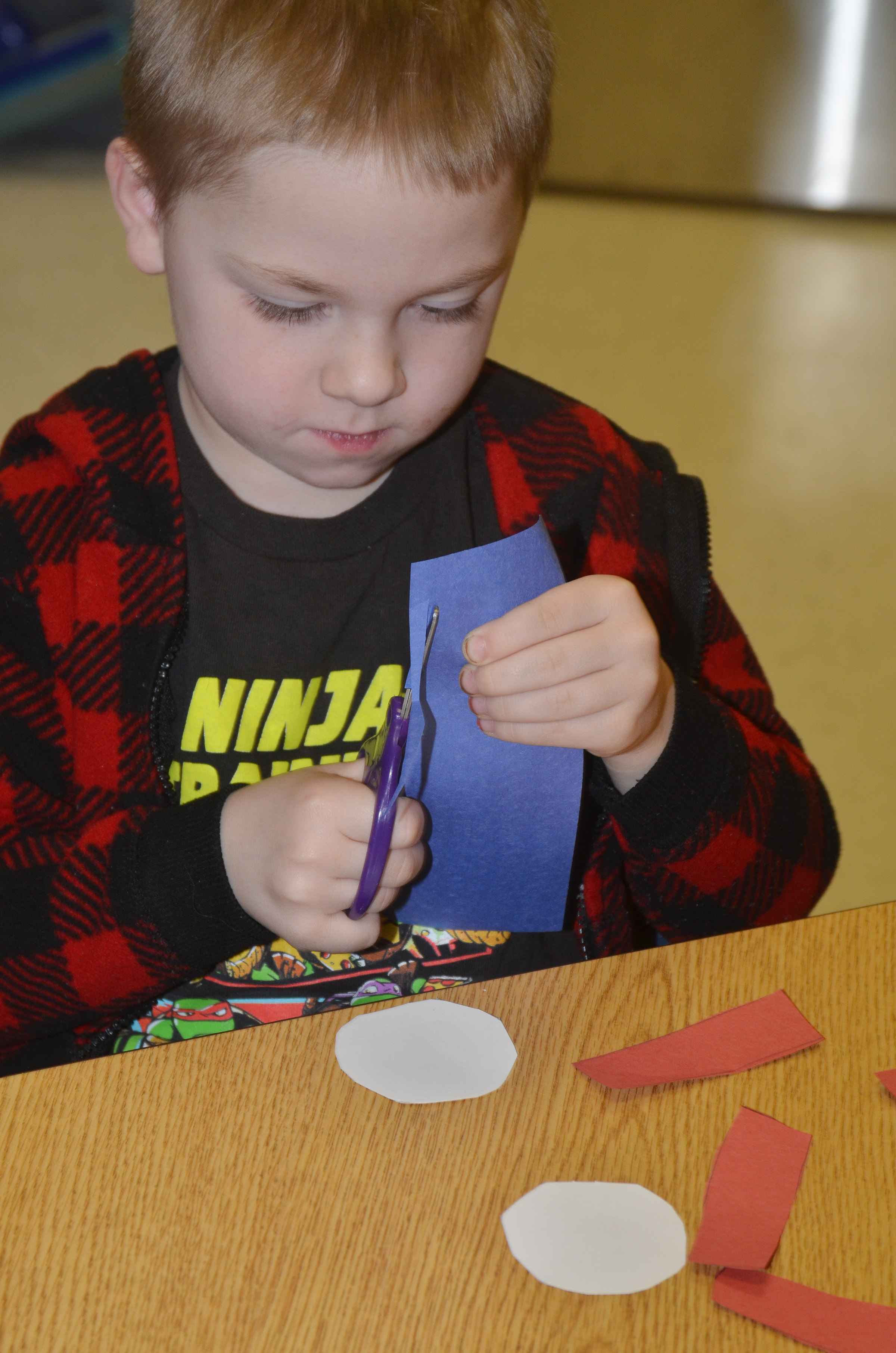 CES kindergartener Noah Milburn cuts out the pieces to his Thing 1 character.